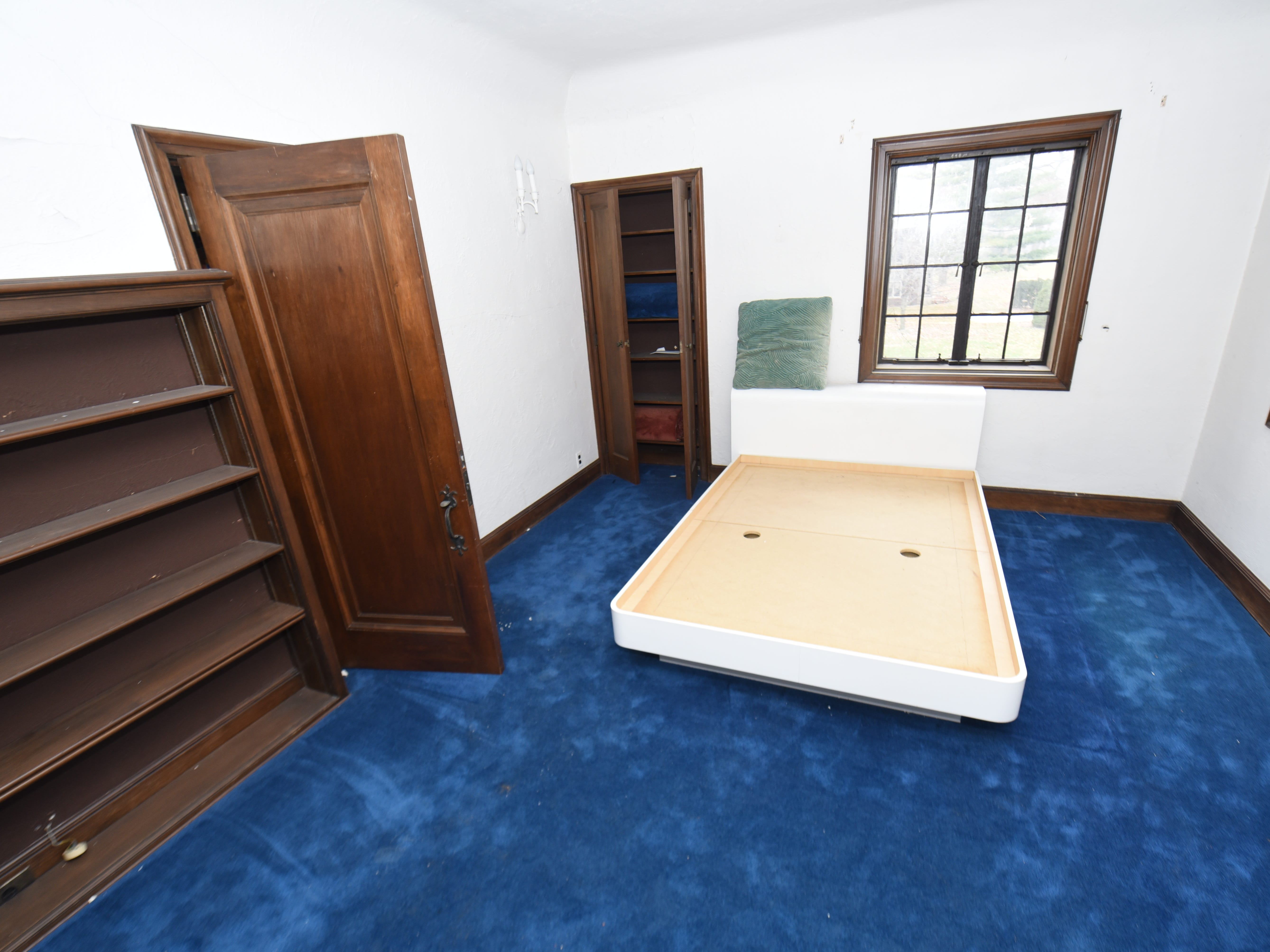 One of the bedrooms has blue carpeting and a bookcase.