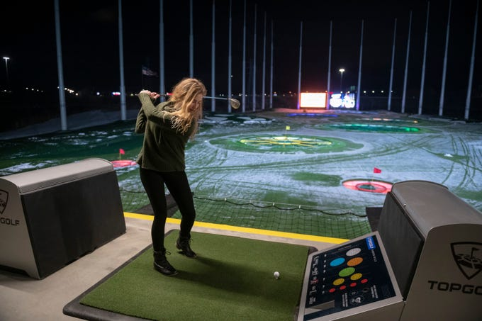 Jackie Zimmerman, of Waterford, tees off from the heated driving range during a preview event at Topgolf, in Auburn Hills, November 28, 2018.