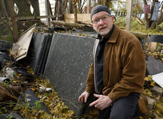 Artist Tim Burke kneels next to 10 tons of granite that he received from the DIA ten years ago. The granite sits behind his former Detroit home, across the street from the Heidelberg Project.