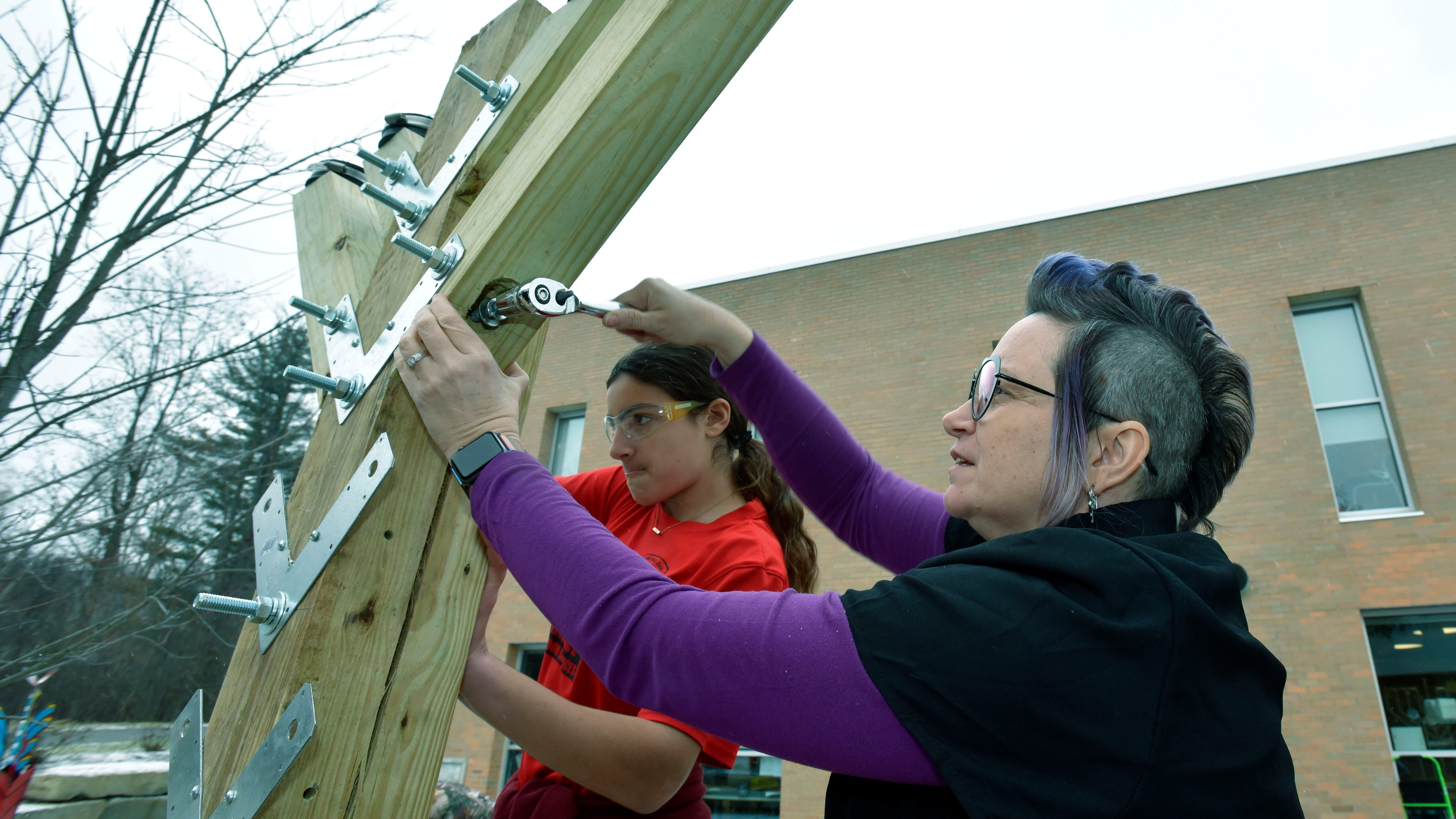 Erica Fischman, left, of Southfield and Dawn Straith of Detroit attach branches to the parade-float menorah. Straith is the Hillel Day School innovation-hub coordinator and educator.