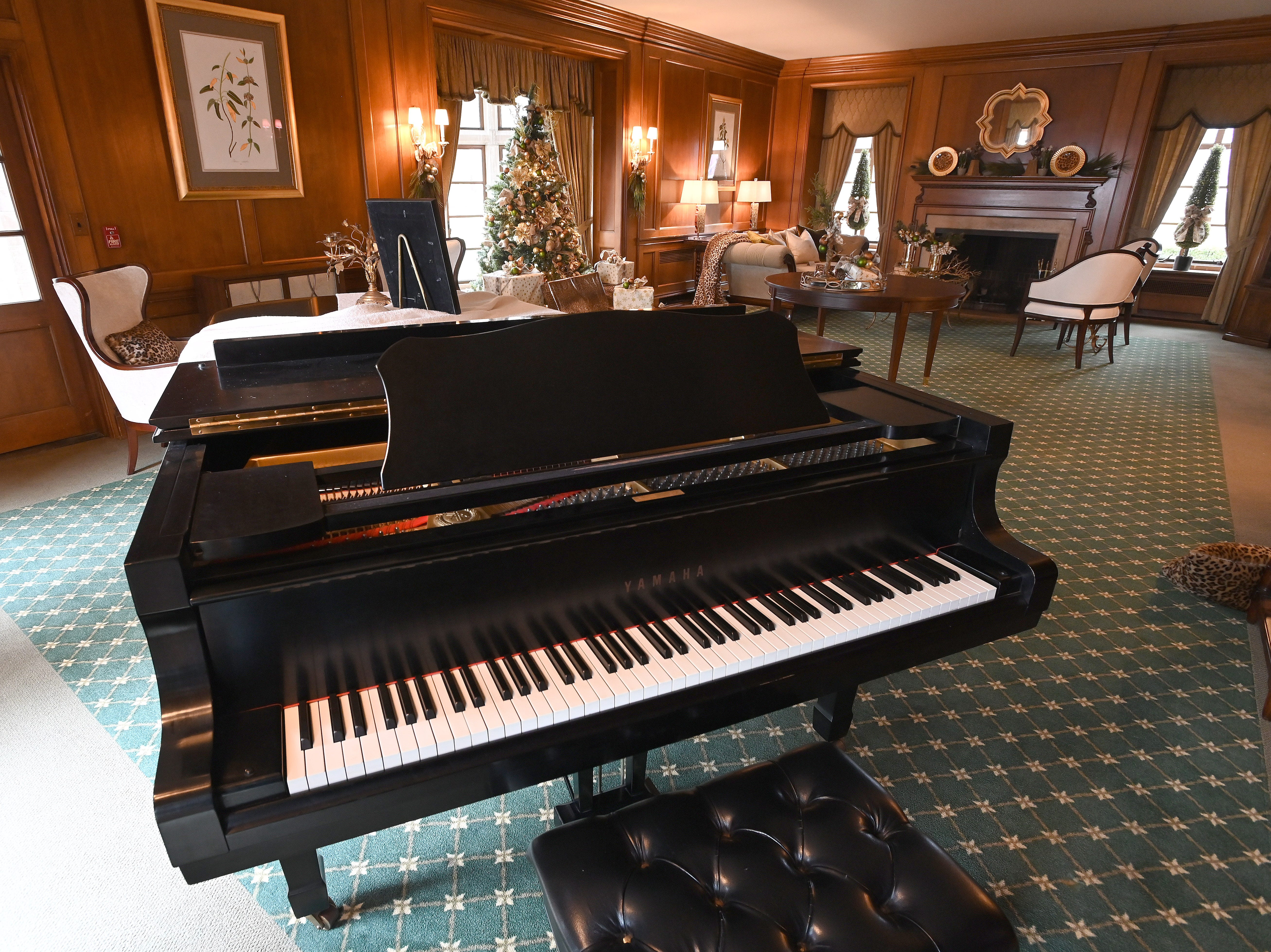 A grand piano dominates one end of the living room where volunteers have gotten to work decorating all the public rooms of the manor.