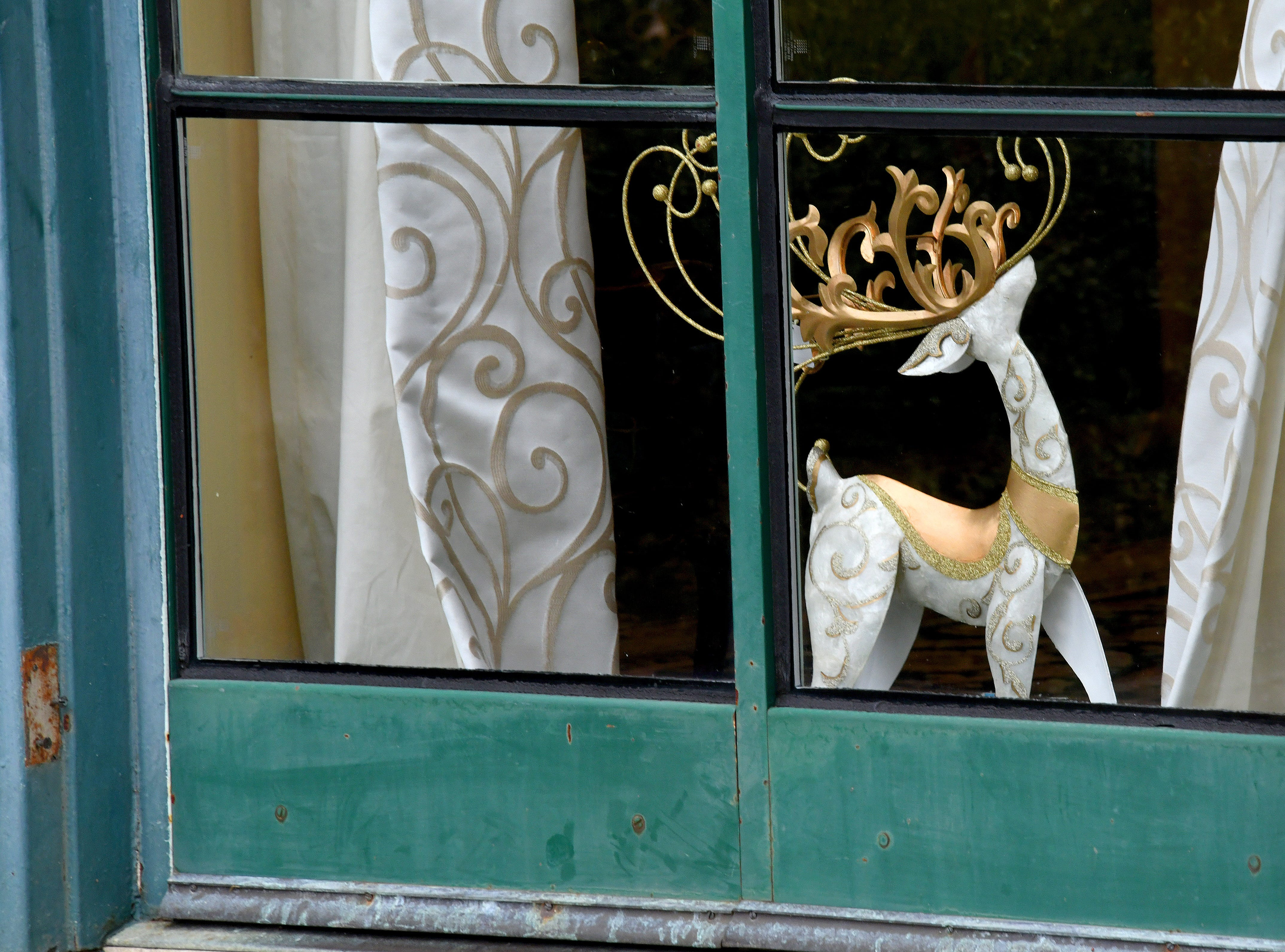 A whimsical reindeer stands on the window sill of the dining room, visible from the rose garden behind the manor.