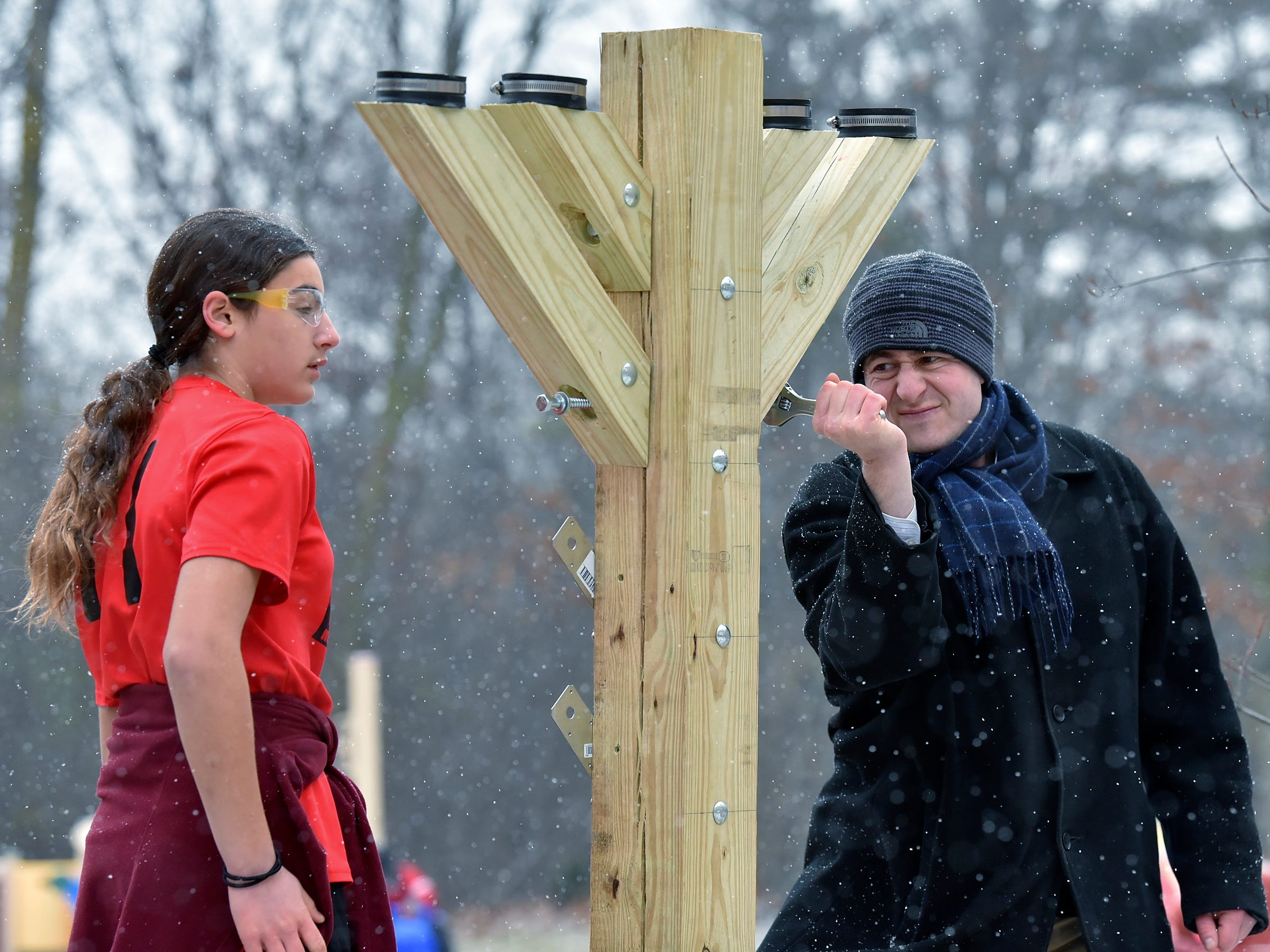 "Erica Fischman, left, of Southfield and Rabbi Shalom Kantor attach branches to the parade-float menorah. West Bloomfield Township's Congregation B'nai Moshe Rabbi Shalom Kantor is assisted by Hillel Day School seventh graders, in Farmington Hills, as they assemble a wooden menorah, Thursday morning, Nov. 29, 2018, on the rear of their ""Parade of Light"" float. The parade, in Oakland County Dec. 8-9, is the final weekend of Hanukkah."