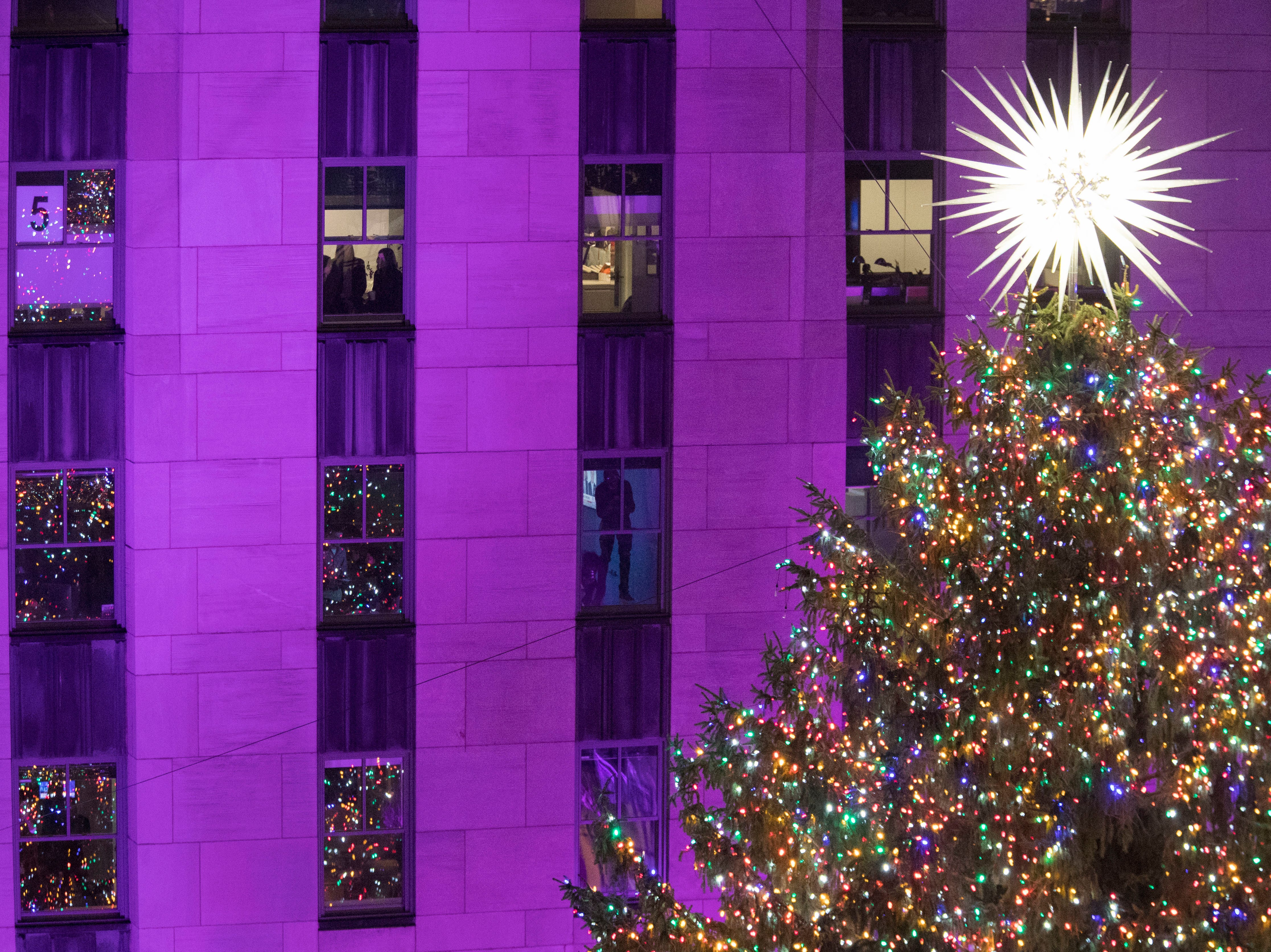 People watch as the Christmas tree is lit during the 86th annual Rockefeller Center Christmas tree lighting ceremony, Wednesday, Nov. 28, 2018, in New York.