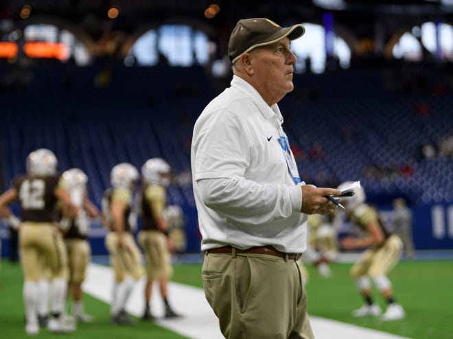 Former Central Bears Coach Mike Owen takes notes as he watches the Central Bears and the Fort Wayne Bishop Dwenger Saints warm-up before competing for the IHSAA Class 4A state title at Lucas Oil Stadium in Indianapolis, Ind., Friday, Nov. 23, 2018.
