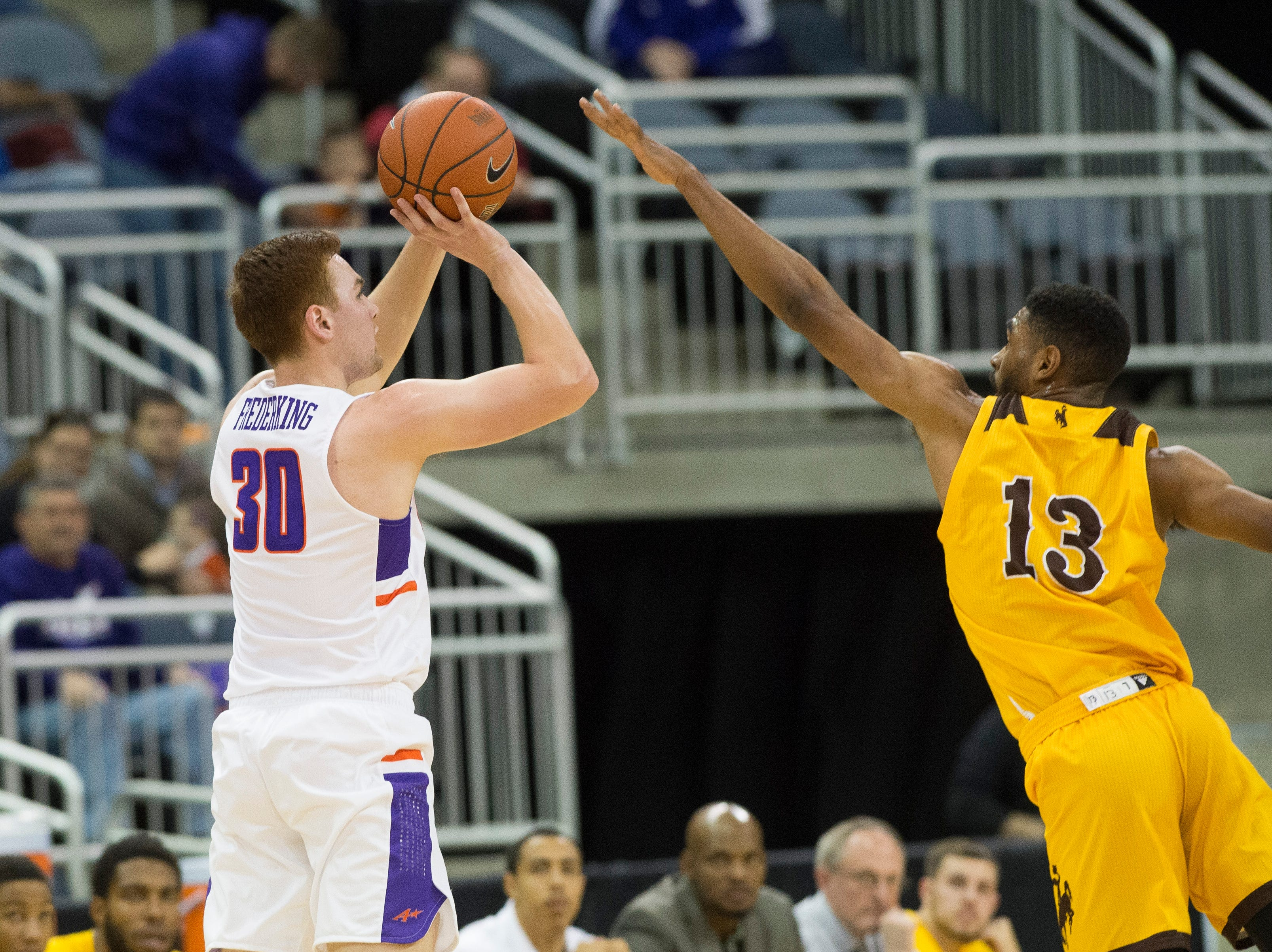 """Wyoming's Trevon """"TJ"""" Taylor (13) attempts to block UE's Noah Frederking (30) 3-point shot during the UE vs Wyoming game at the Ford Center Wednesday, Nov. 28, 2018. UE won 86-76."""