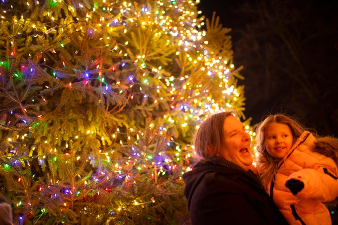 Melora Austin, 5, and Christopher Bass, both of Evansville, pose for Victoria Austin, Melora's mom, after the  City of Evansville's annual Christmas Tree lighting ceremony outside the Civic Center Wednesday evening.
