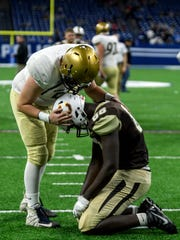 Bishop Dwenger's Grant Sorg (51) gives Central's Rayzel Joiner (88) a pat on the back following the Bears' 16-10 loss in the quadruple overtime Class 4A state championship match at Lucas Oil Stadium in Indianapolis, Ind., Friday, Nov. 23, 2018.