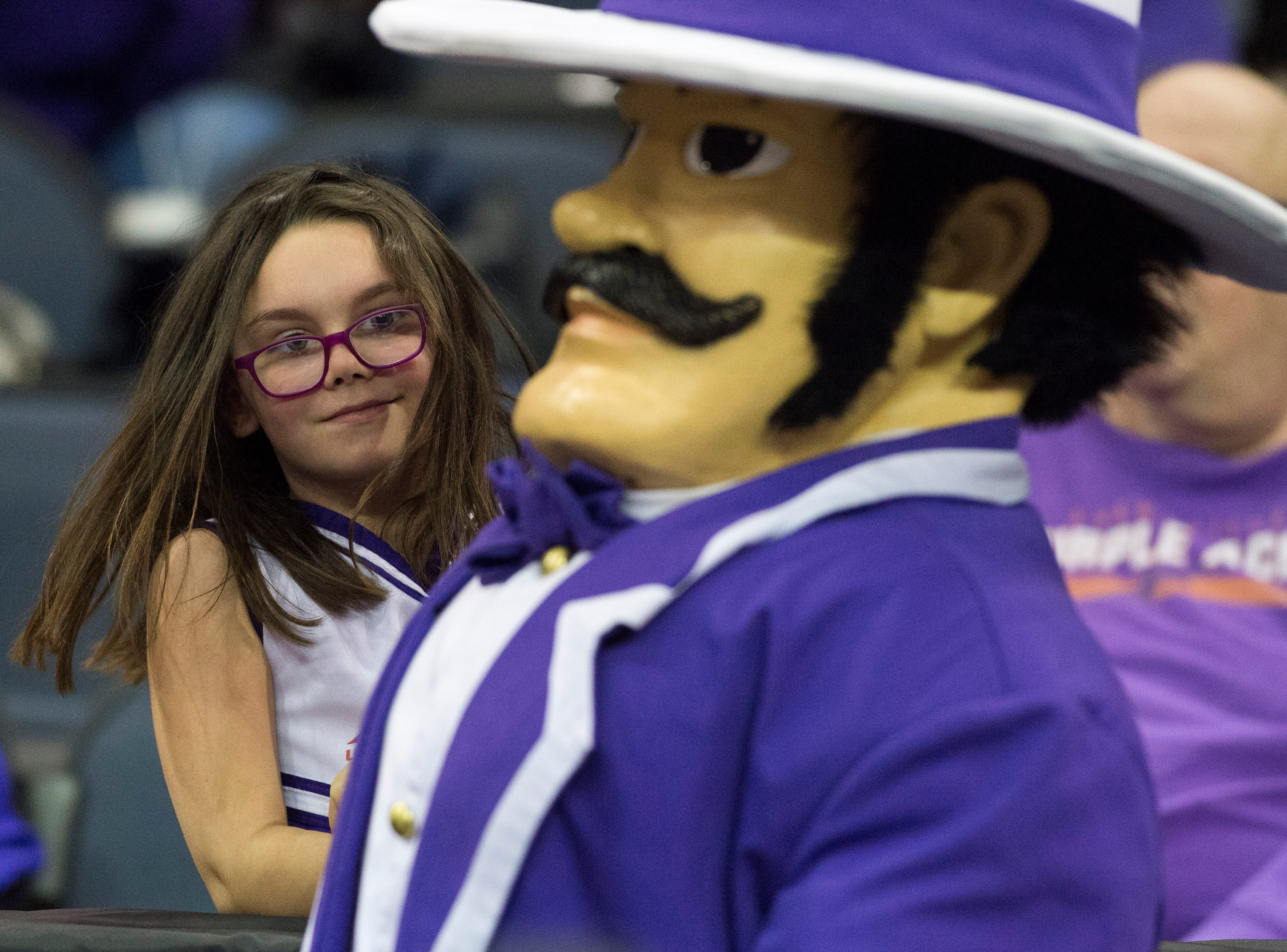 University of Evansville basketball fan Jasmine Bivin, 7, smiles as UE's mascot Ace Purple walks by during the UE vs Wyoming game at the Ford Center Wednesday, Nov. 28, 2018. UE won 86-76.