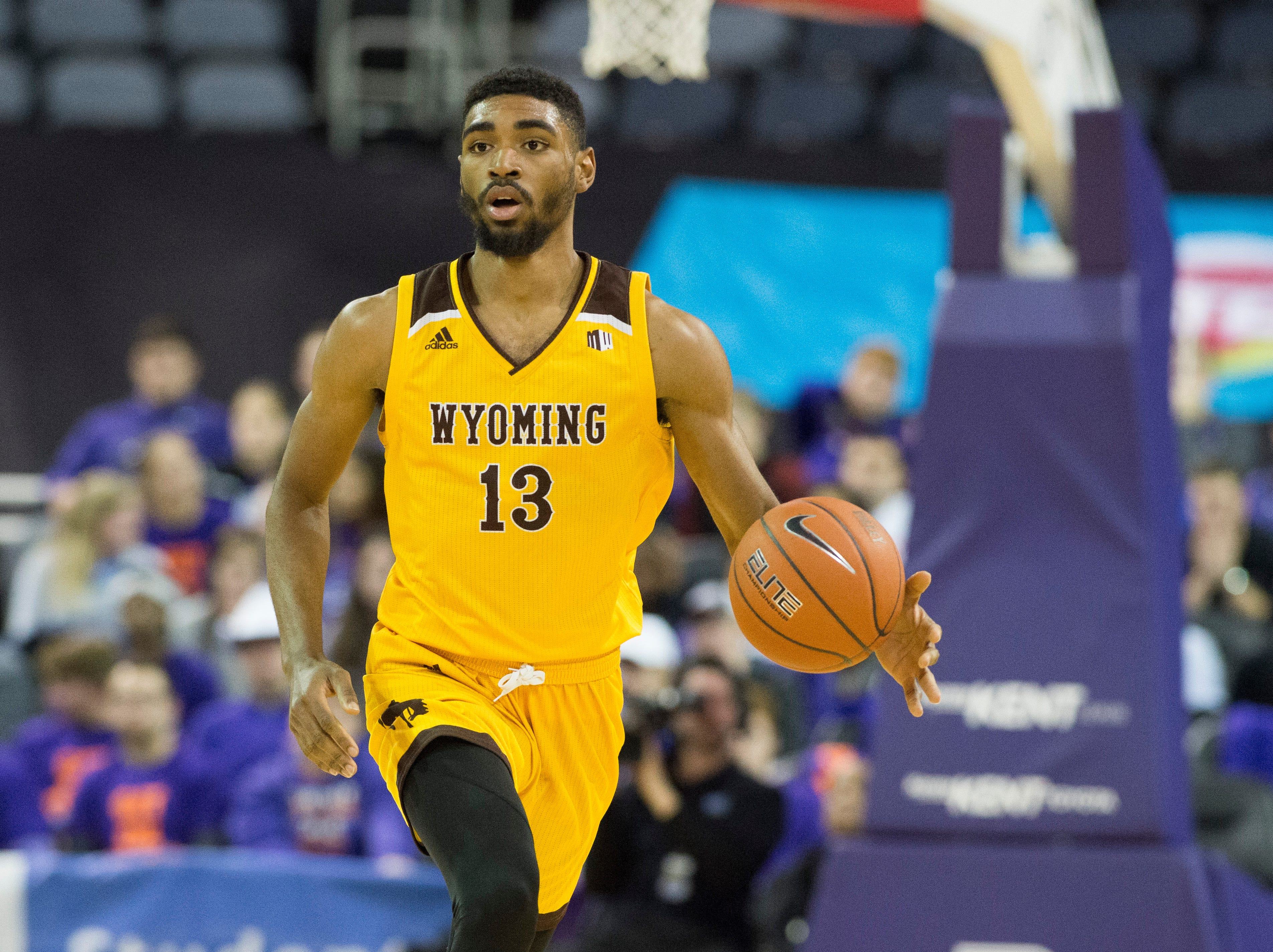 """Wyoming's Trevon """"TJ"""" Taylor (13) eyes the court as he dribbles the ball during the UE vs Wyoming game at the Ford Center Wednesday, Nov. 28, 2018. UE won 86-76."""