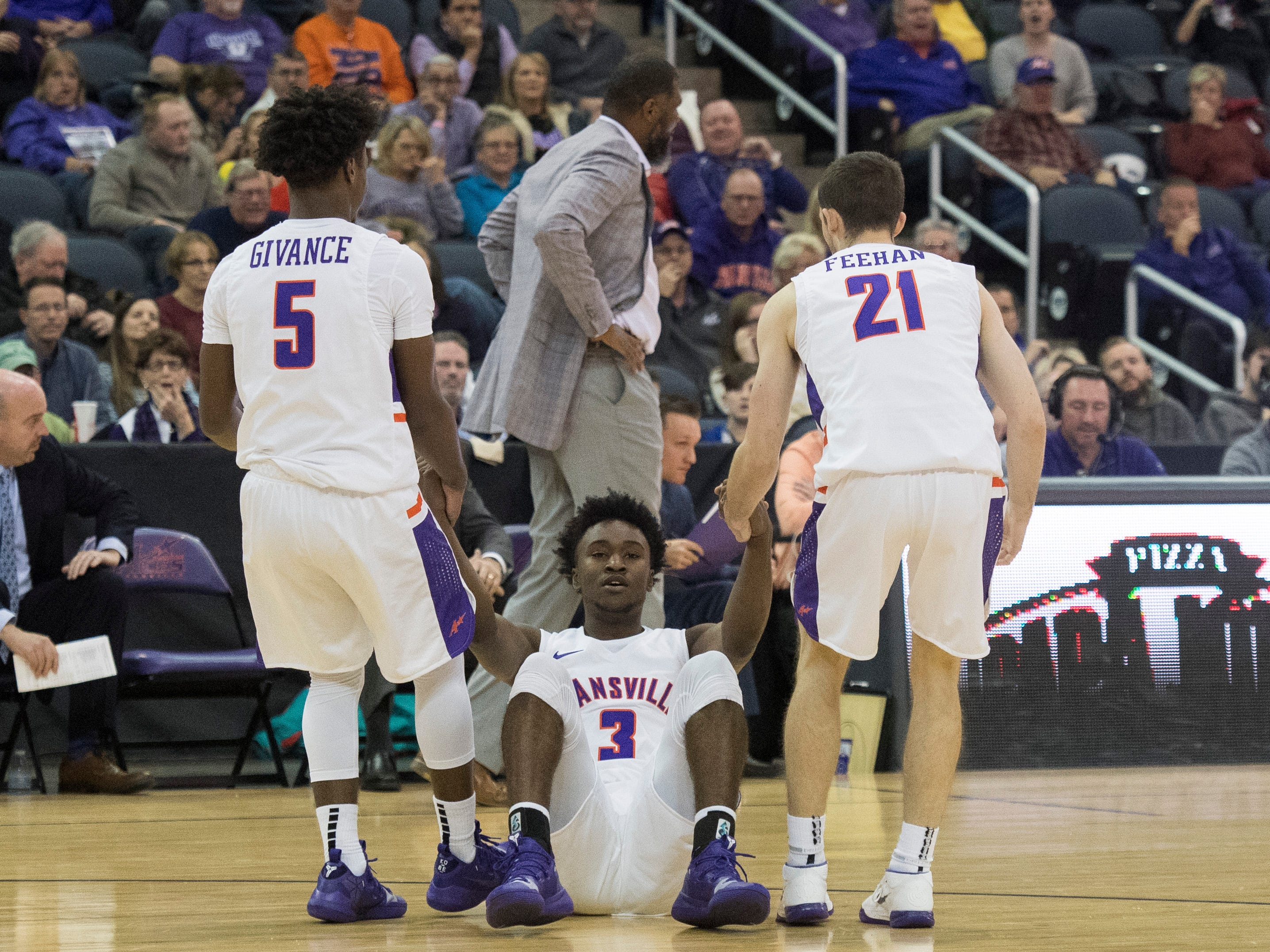 UE's Shamar Givance (5) and Shea Feehan (21) help teammate UE's Jawaun Newton (3) up off the court  during the UE vs Wyoming game at the Ford Center Wednesday, Nov. 28, 2018. UE won 86-76.