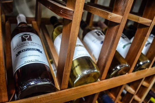 Bottles of Ski Lodge Winery wine sit on racks at the winery. The wine list includes 16 different flavors.