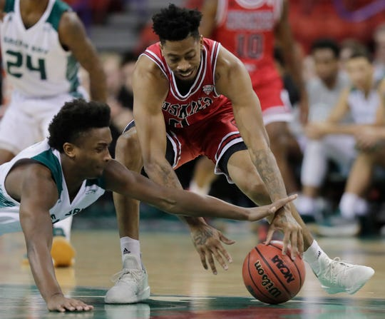 Northern Illinois guard Dante Thorpe (0) and Phoenix guard PJ Pipes (2) dive for a loose ball in UWGB's 85-83 win.