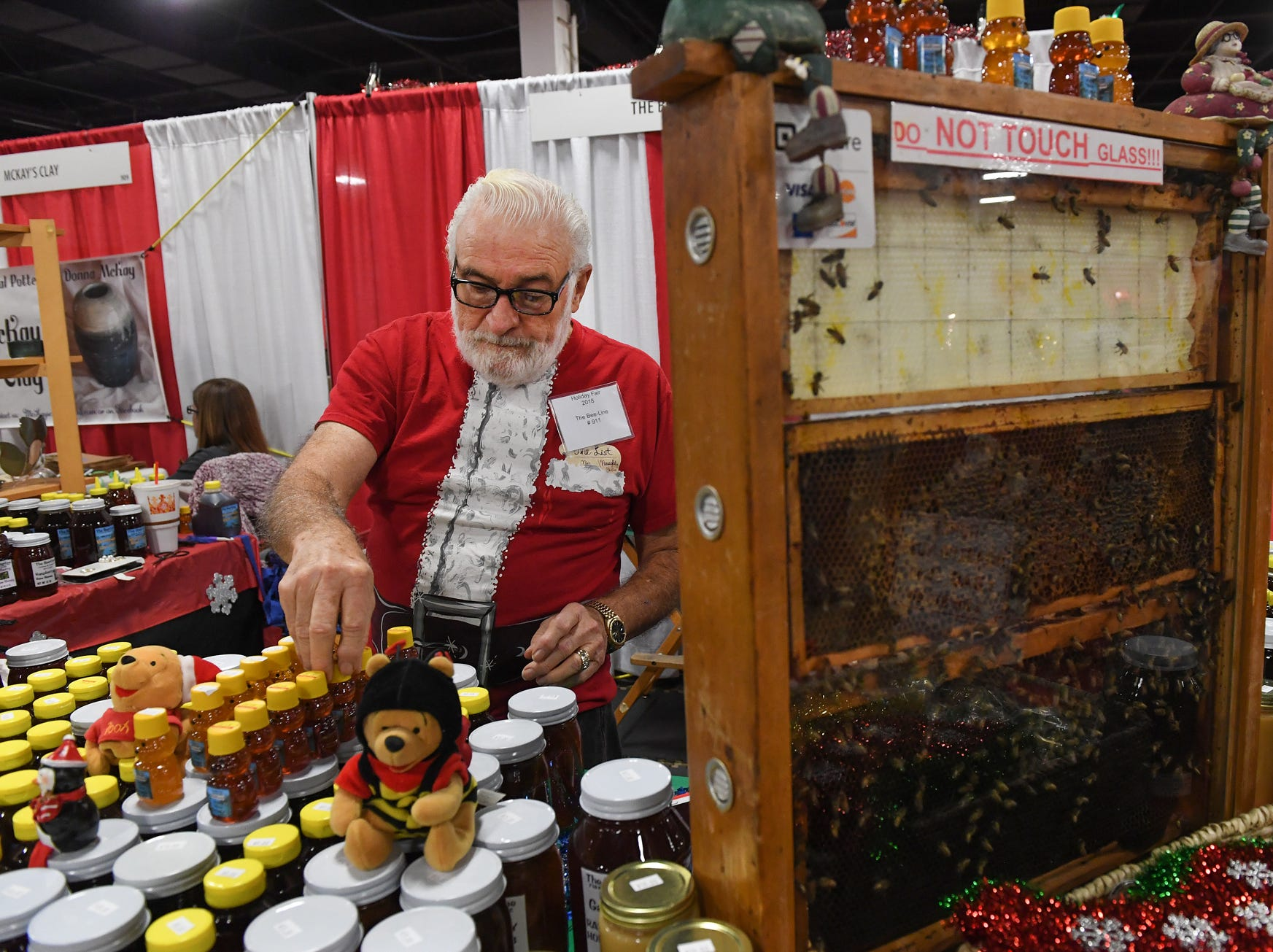 Beekeeper Lewis Mahaffey organizes honey in his booth during the 48th annual Holiday Fair at the Greenville Convention Center Thursday, November 29,  2018.