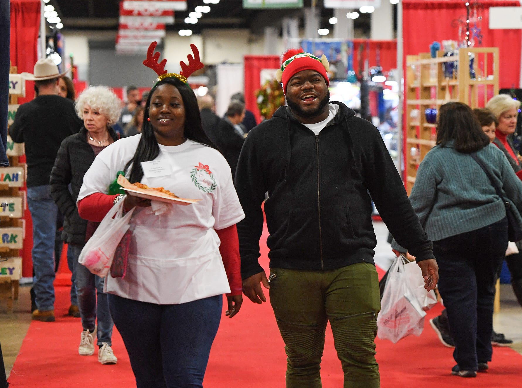 Leo Ellis and Asia Davis walk the aisle during the 48th annual Holiday Fair at the Greenville Convention Center Thursday, November 29,  2018.