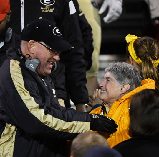 Greer High football fan Sarah McIntyre, right, shares a laugh with assistant coach Travis Perry following the Yellow Jackets' first-round playoff victory over Pickens Nov. 9.