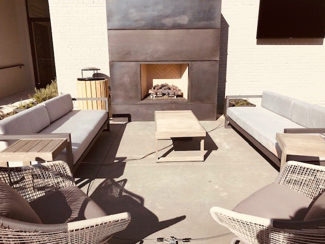 An outside area features a fireplace and couches.