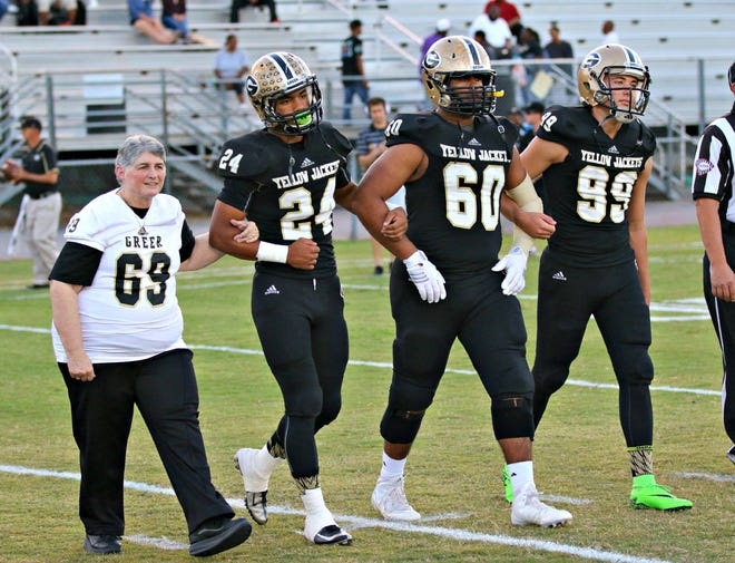 Greer High football fan Sarah McIntyre takes the field with Yellow Jacket captains Adrian McGee (24), Noah Hannon (60) and Andrew Messer (99) before a 2015 game.