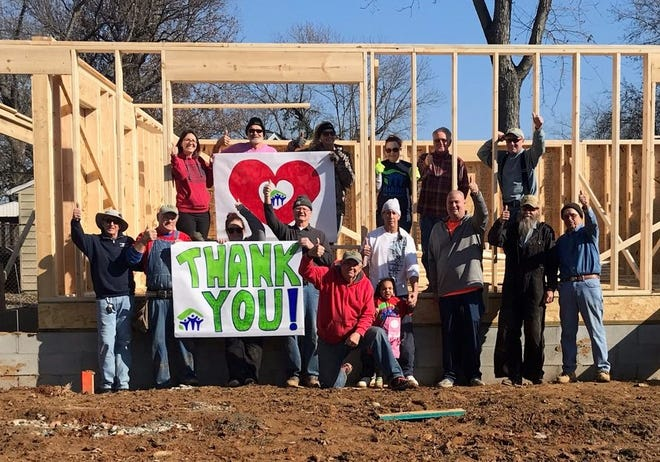 "Habitat for Humanity of Henderson volunteers hold up a banner saying ""Thank You"" after their stolen tools were replaced."