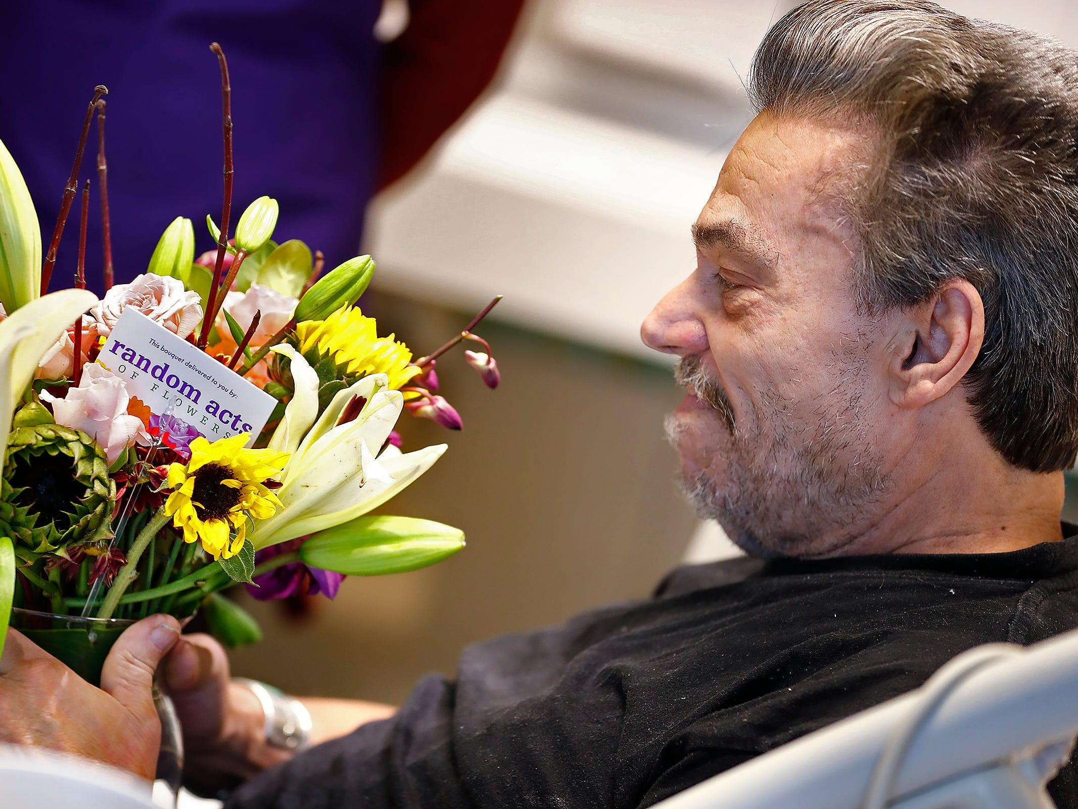 Robert Eastes, right, smiles as he looks at the bouquet of flowers delivered to him by Random Acts of Flowers volunteers, at Sidney & Lois Eskenazi Hospital, Thursday, Nov. 29, 2018.  The newest branch of the national floral nonprofit has been delivering the flowers to patients to offer hope, encouragement and smiles, for about two years.