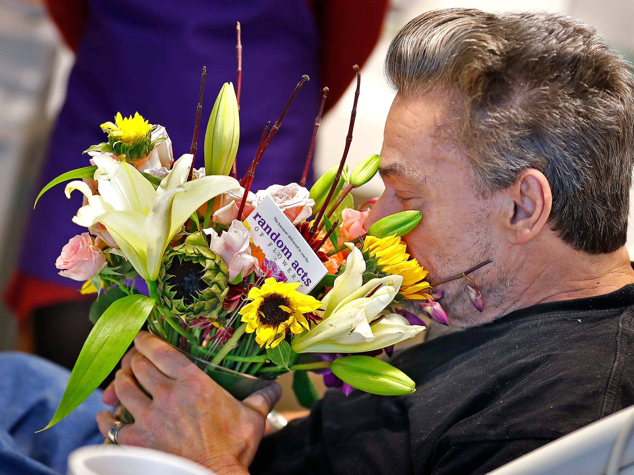 Robert Eastes, right, takes a big sniff of the flowers delivered to him by Random Acts of Flowers volunteers, at Sidney & Lois Eskenazi Hospital, Thursday, Nov. 29, 2018.  The newest branch of the national floral nonprofit has been delivering the flowers to patients to offer hope, encouragement and smiles, for about two years.