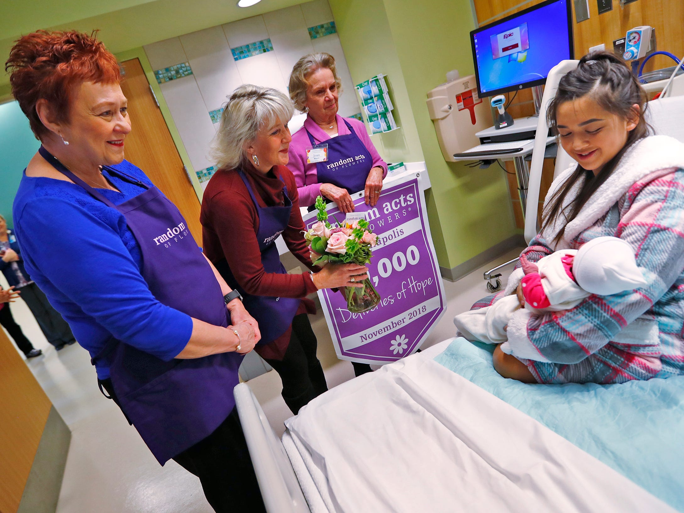 Kathy Bradfield, from left, Claire Alexander, and Joan Perry, with Random Acts of Flowers, deliver their 50,000th bouquet of flowers to Ana Ramos, right, and her new daughter, Keilani Pena Ramos, at Sidney & Lois Eskenazi Hospital, Thursday, Nov. 29, 2018.  The newest branch of the national floral nonprofit has been delivering the flowers to patients to offer hope, encouragement and smiles, for about two years.