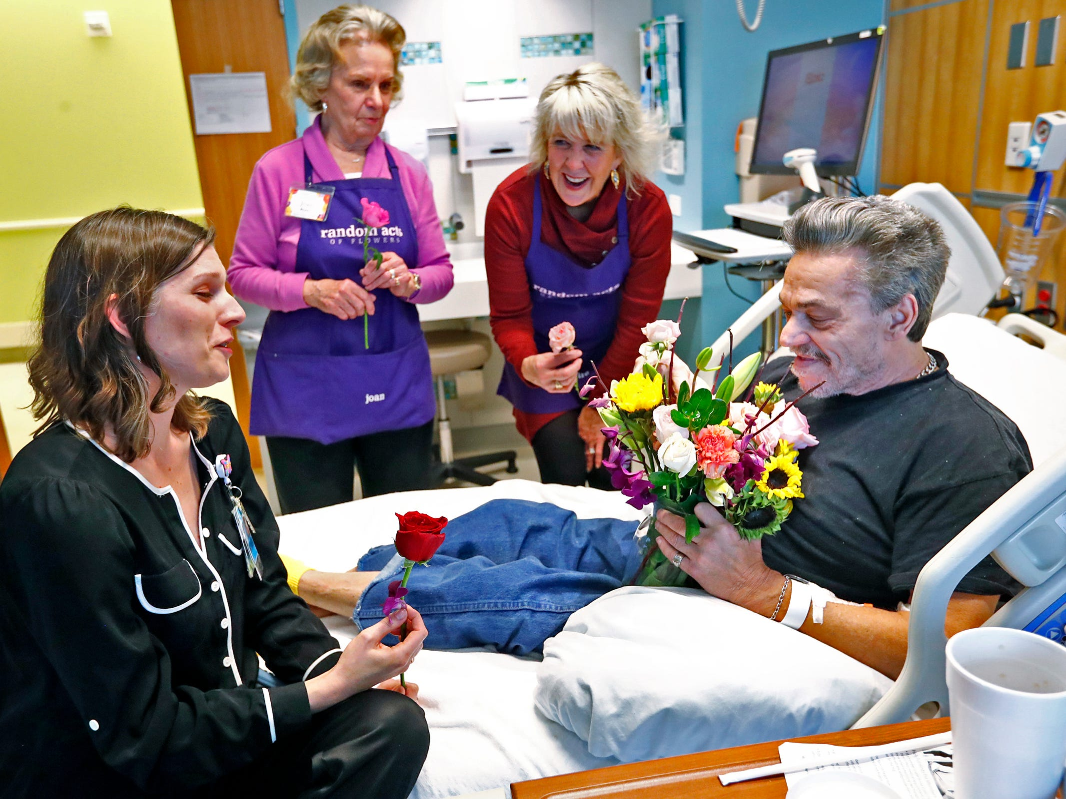 Natalie George Dykstra, from left, with Eskenazi's Office of Patient Experience, joins Joan Perry, and Claire Alexander, with Random Acts of Flowers, to deliver a bouquet of flowers to Robert Eastes, right, at Sidney & Lois Eskenazi Hospital, Thursday, Nov. 29, 2018.  The newest branch of the national floral nonprofit has been delivering the flowers to patients to offer hope, encouragement and smiles, for about two years.  Eastes also shared a flower with each of the women, and a woman photographer.