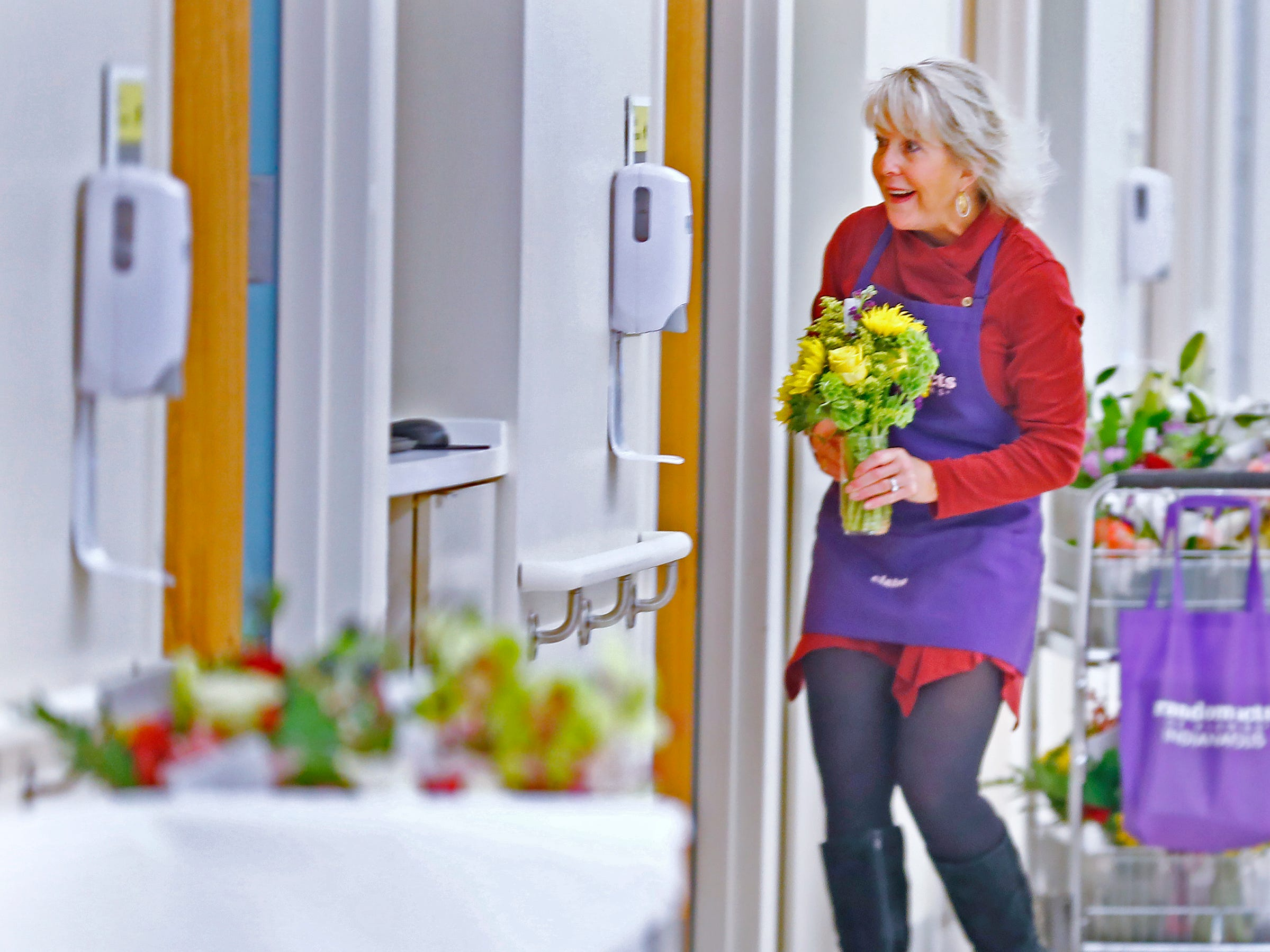 Claire Alexander, with Random Acts of Flowers, gets ready to deliver flowers to a patient, at Sidney & Lois Eskenazi Hospital, Thursday, Nov. 29, 2018.  The newest branch of the national floral nonprofit has been delivering the flowers to patients to offer hope, encouragement and smiles, for about two years.  This day, Random Acts of Flowers delivered their 50,000th bouquet.