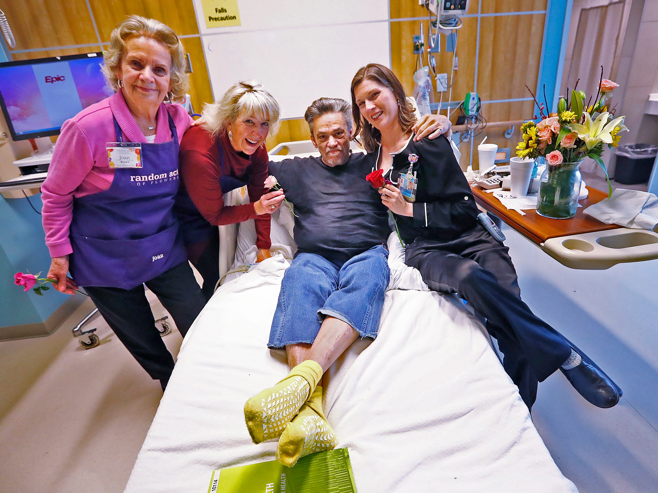 Joan Perry, from left, and Claire Alexander, with Random Acts of Flowers, and Natalie George Dykstra, right, with Eskenazi's Office of Patient Experience, pose with patient Robert Eastes, at Sidney & Lois Eskenazi Hospital, Thursday, Nov. 29, 2018, after delivering a bouquet of flowers to him.  The newest branch of the national floral nonprofit has been delivering the flowers to patients to offer hope, encouragement and smiles, for about two years.  Eastes also shared a flower with each of the women, and a woman photographer.