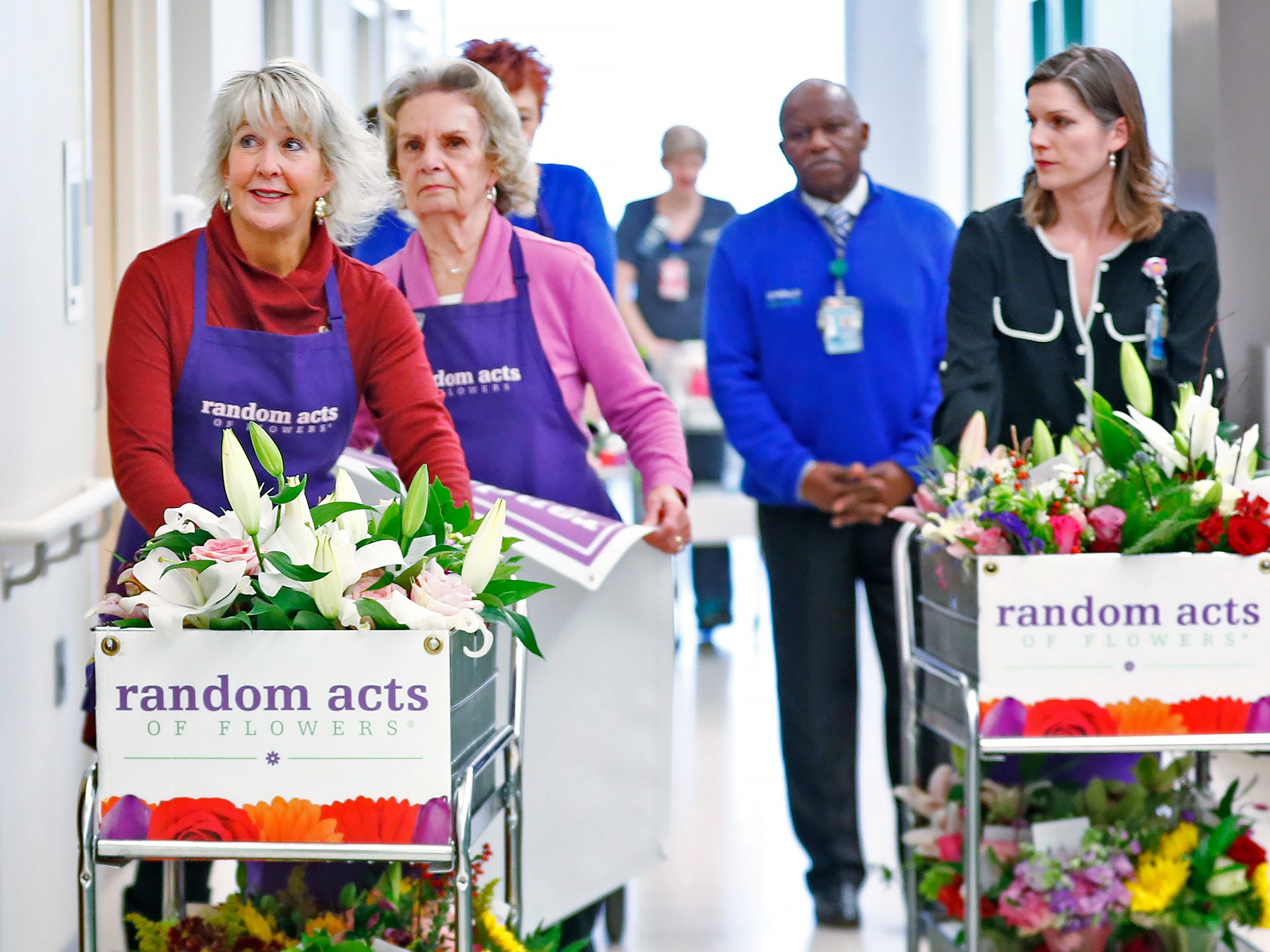Claire Alexander, left, Joan Perry, center, with Random Acts of Flowers, and Natalie George Dykstra, with Eskenazi's Office of Patient Experience, right, and others deliver flowers to patients, at Sidney & Lois Eskenazi Hospital, Thursday, Nov. 29, 2018.  The newest branch of the national floral nonprofit has been delivering the flowers to patients to offer hope, encouragement and smiles, for about two years.  This day, Random Acts of Flowers delivered their 50,000th bouquet.