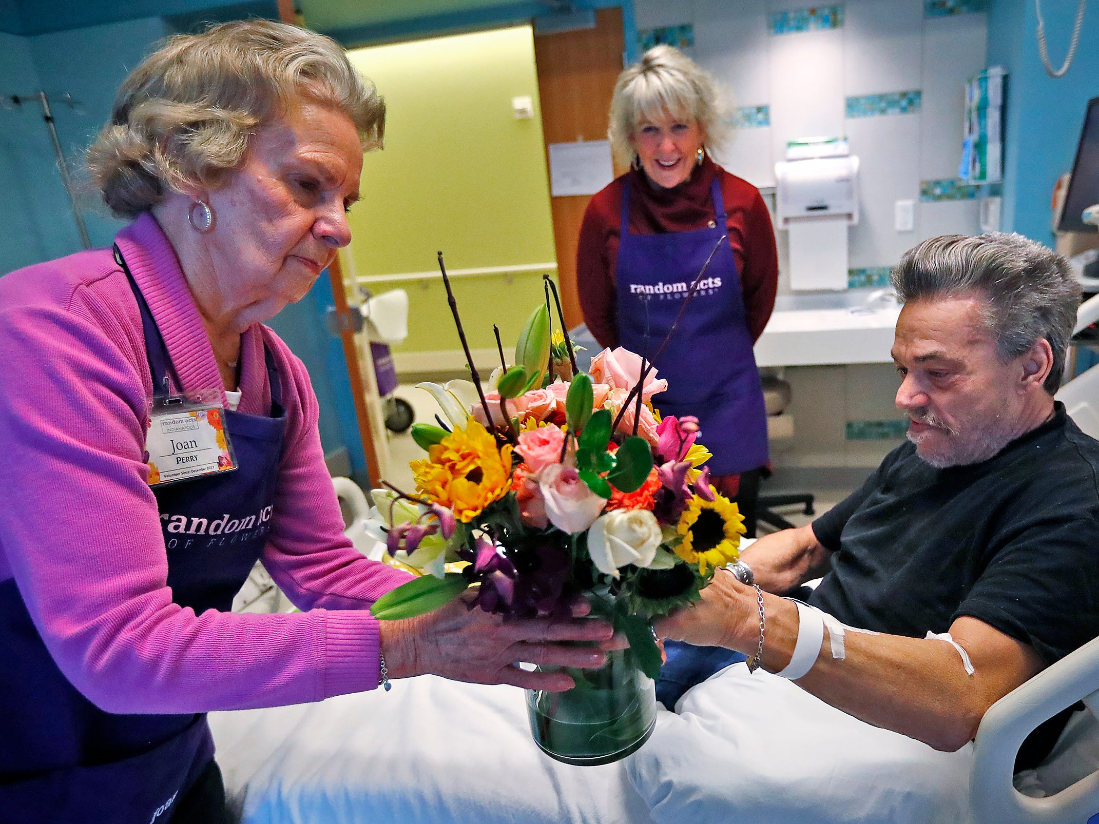 Joan Perry, from left, and Claire Alexander, with Random Acts of Flowers, deliver a bouquet of flowers to Robert Eastes, right, at Sidney & Lois Eskenazi Hospital, Thursday, Nov. 29, 2018.  The newest branch of the national floral nonprofit has been delivering the flowers to patients to offer hope, encouragement and smiles, for about two years.