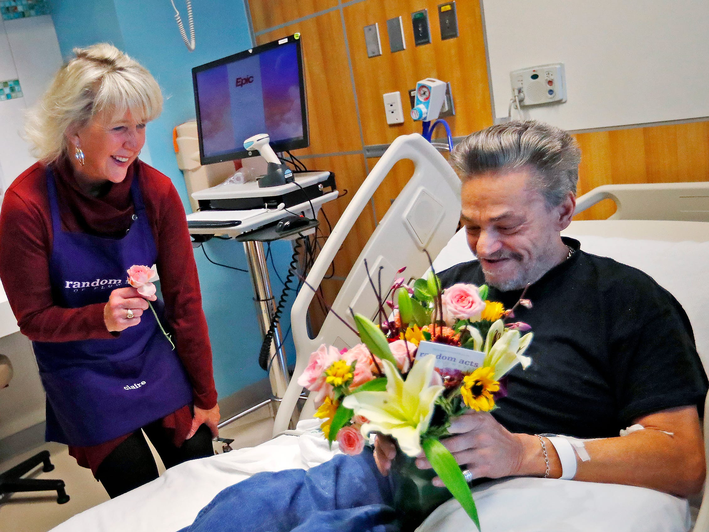 Claire Alexander, with Random Acts of Flowers, joins other volunteers to deliver a bouquet of flowers to Robert Eastes, right, at Sidney & Lois Eskenazi Hospital, Thursday, Nov. 29, 2018.  The newest branch of the national floral nonprofit has been delivering the flowers to patients to offer hope, encouragement and smiles, for about two years.  Eastes also shared a flower with each of the women delivering to him.