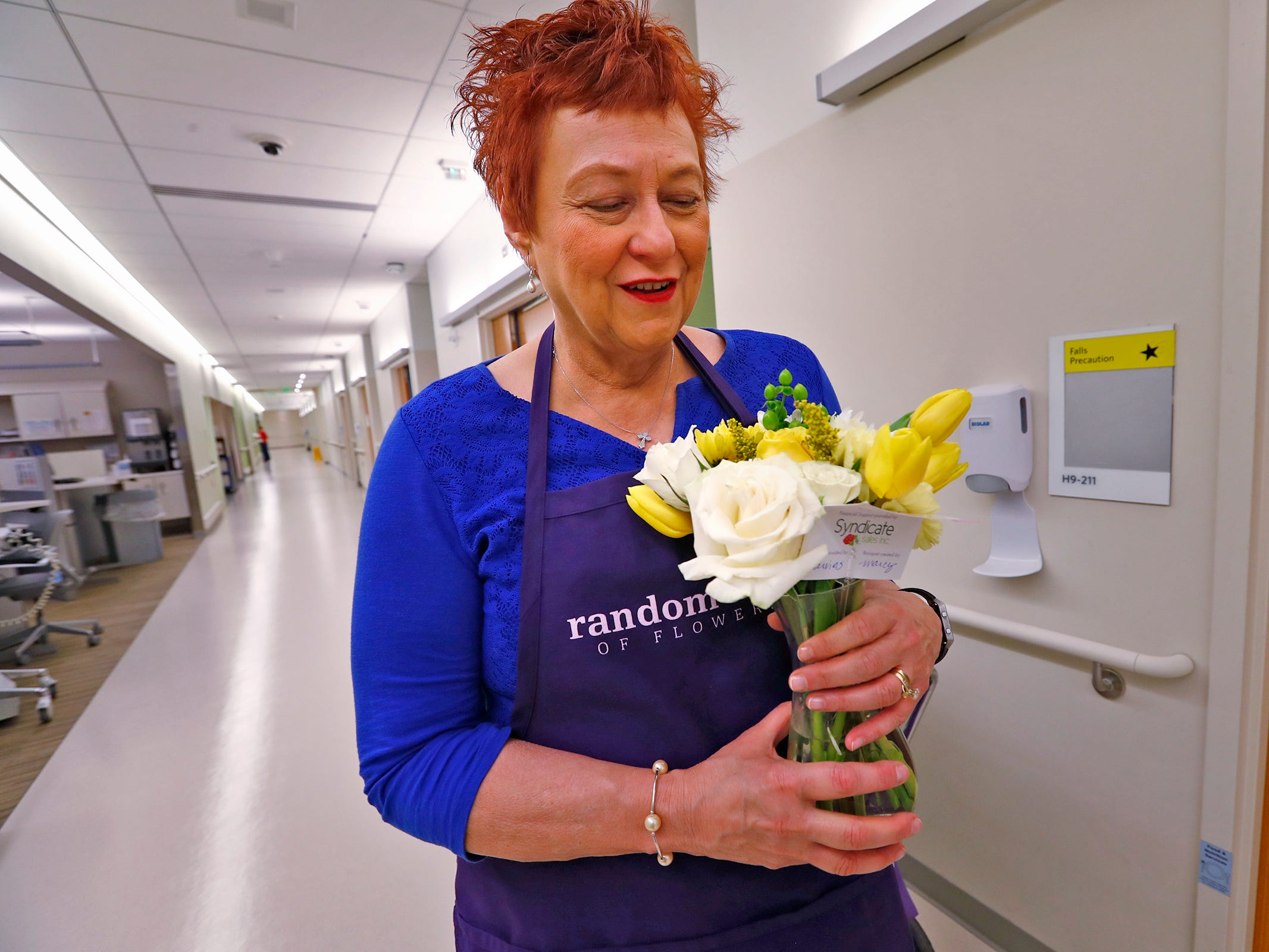 Kathy Bradfield, with Random Acts of Flowers, gets ready to deliver flowers to a patient, at Sidney & Lois Eskenazi Hospital, Thursday, Nov. 29, 2018.  The newest branch of the national floral nonprofit has been delivering the flowers to patients to offer hope, encouragement and smiles, for about two years. This day, Random Acts of Flowers delivered their 50,000th bouquet.