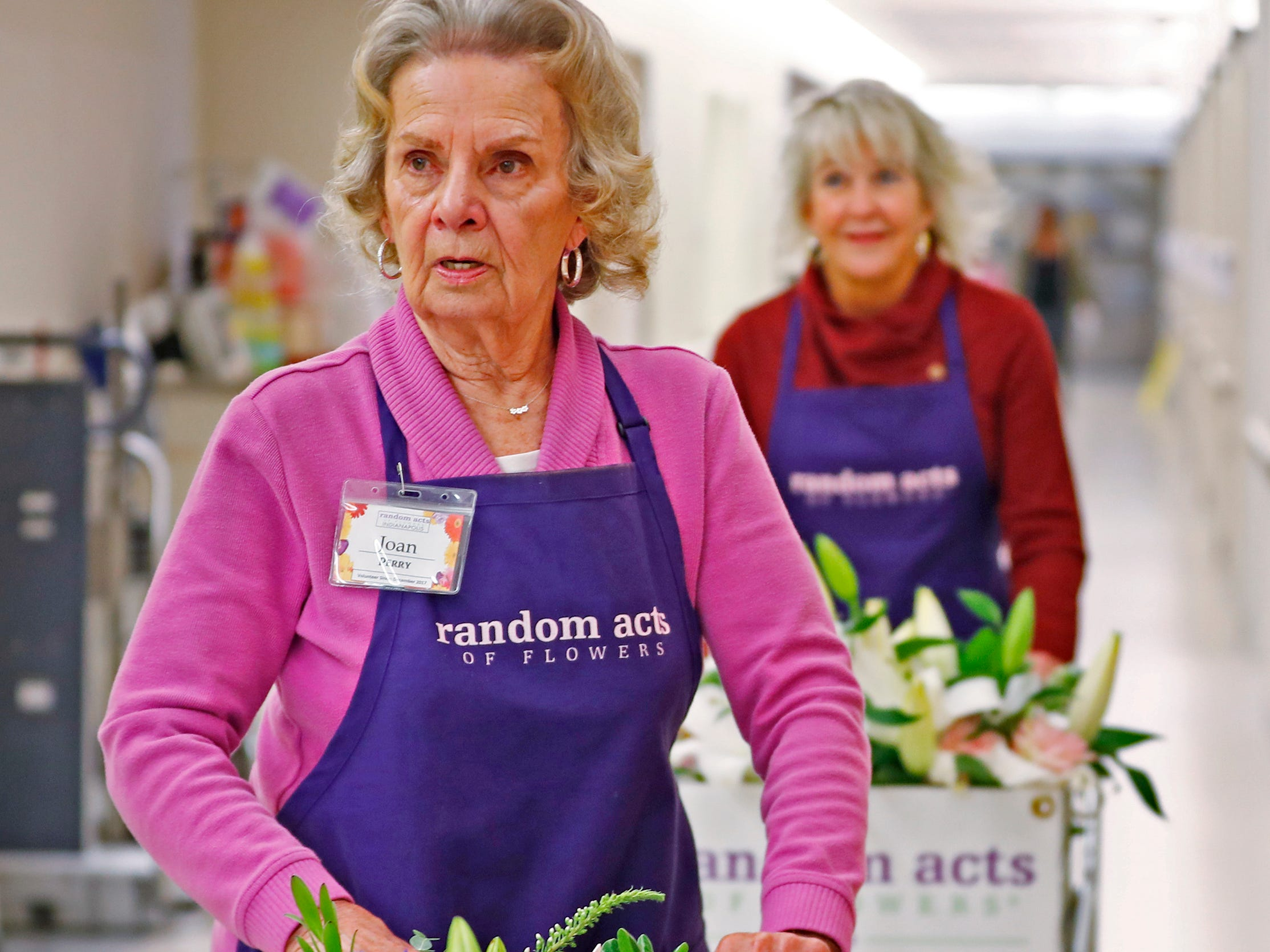 Joan Perry, left, and Claire Alexander, with Random Acts of Flowers, deliver flowers to patients, at Sidney & Lois Eskenazi Hospital, Thursday, Nov. 29, 2018.  The newest branch of the national floral nonprofit has been delivering the flowers to patients to offer hope, encouragement and smiles, for about two years.  This day, Random Acts of Flowers delivered their 50,000th bouquet.