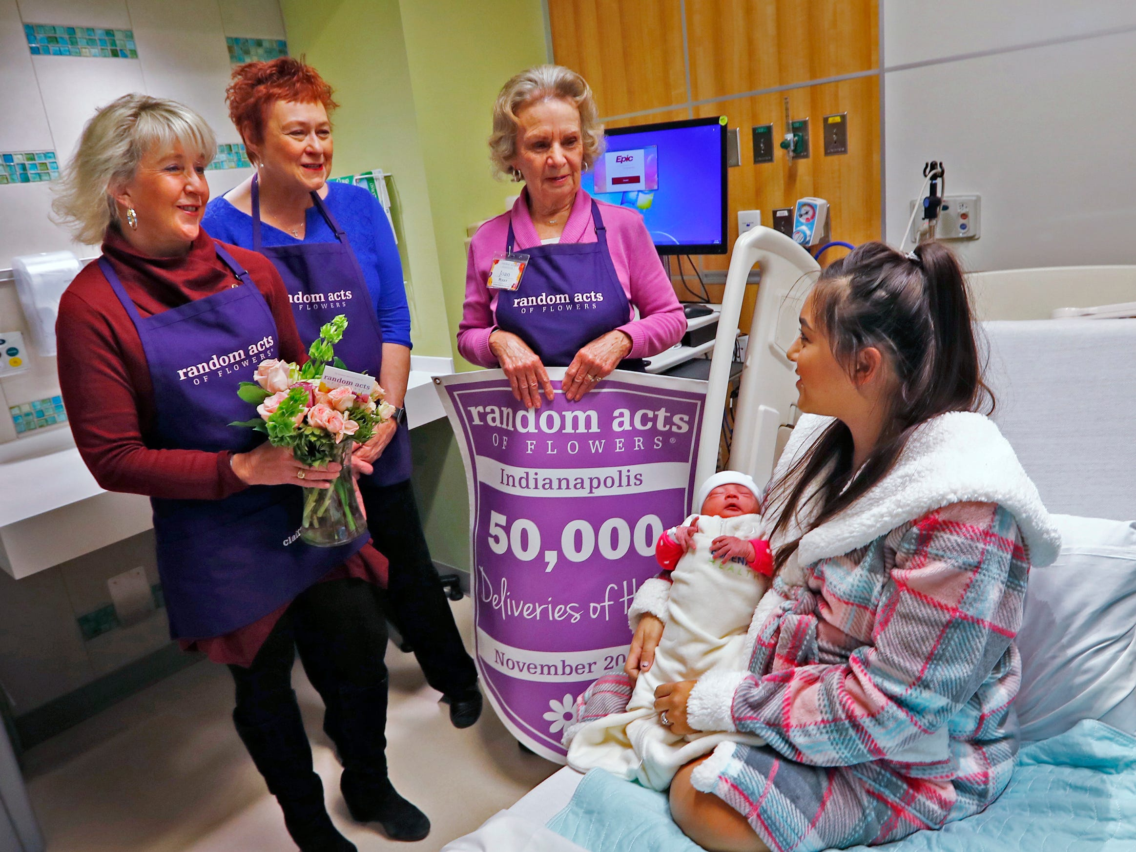 Claire Alexander, from left, Kathy Bradfield, and Joan Perry, with Random Acts of Flowers, deliver their 50,000th bouquet of flowers to Ana Ramos, right, and her new daughter, Keilani Pena Ramos, at Sidney & Lois Eskenazi Hospital, Thursday, Nov. 29, 2018.  The newest branch of the national floral nonprofit has been delivering the flowers to patients to offer hope, encouragement and smiles, for about two years.