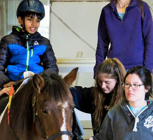 Jaden Randhir enjoys the view from the back of a mature gelding named Charlie, led by horse leader Becca Wilhelm (right) with Haley Paulson serving as a sidewalker.