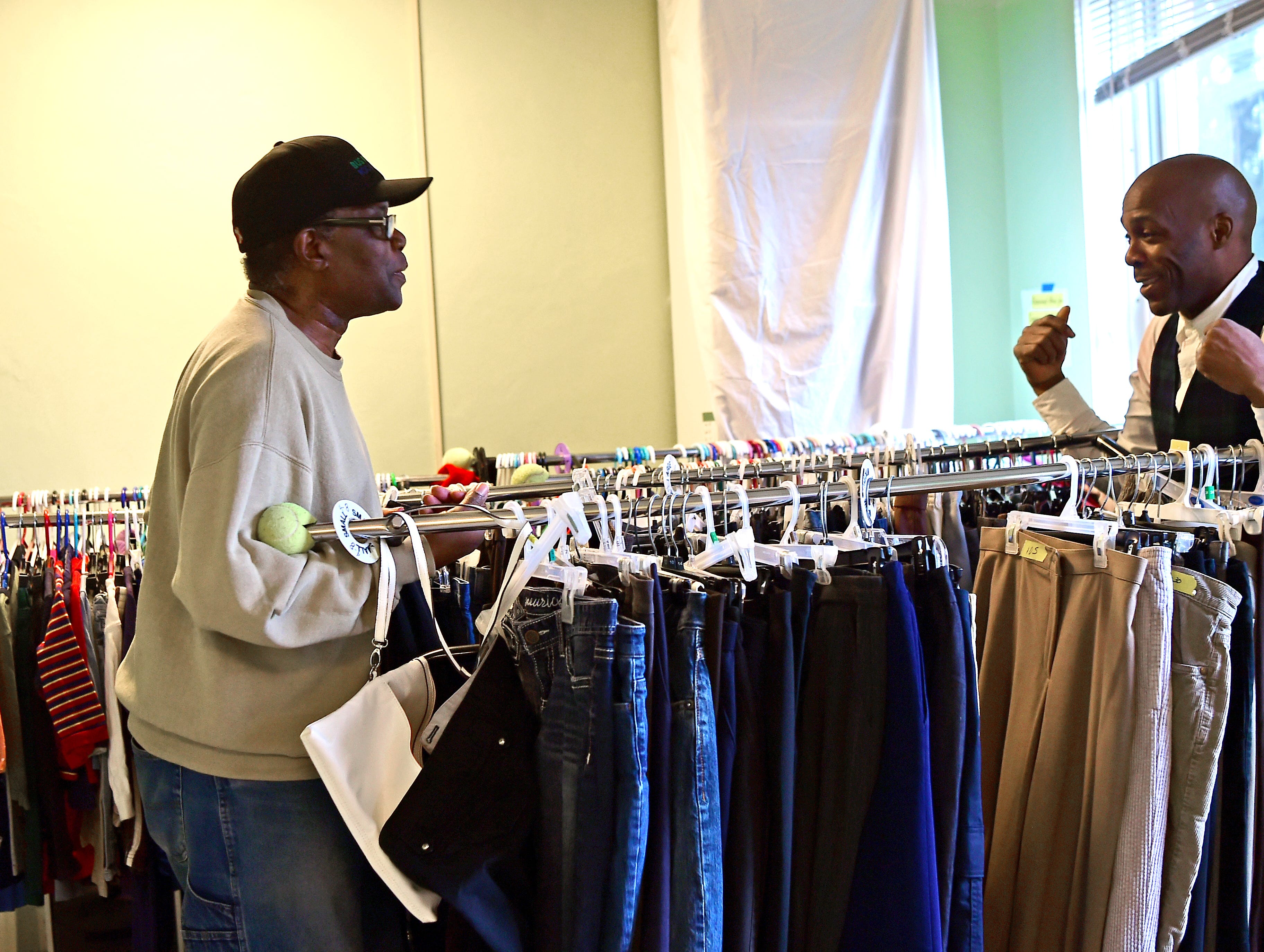 Emmanuel McBean and Alex Williams move racks of clothes as Catholic Charities of Tompkins/Tioga staff and volunteers work at readying winter clothing donations in Ithaca on Thursday, November 29, 2018.