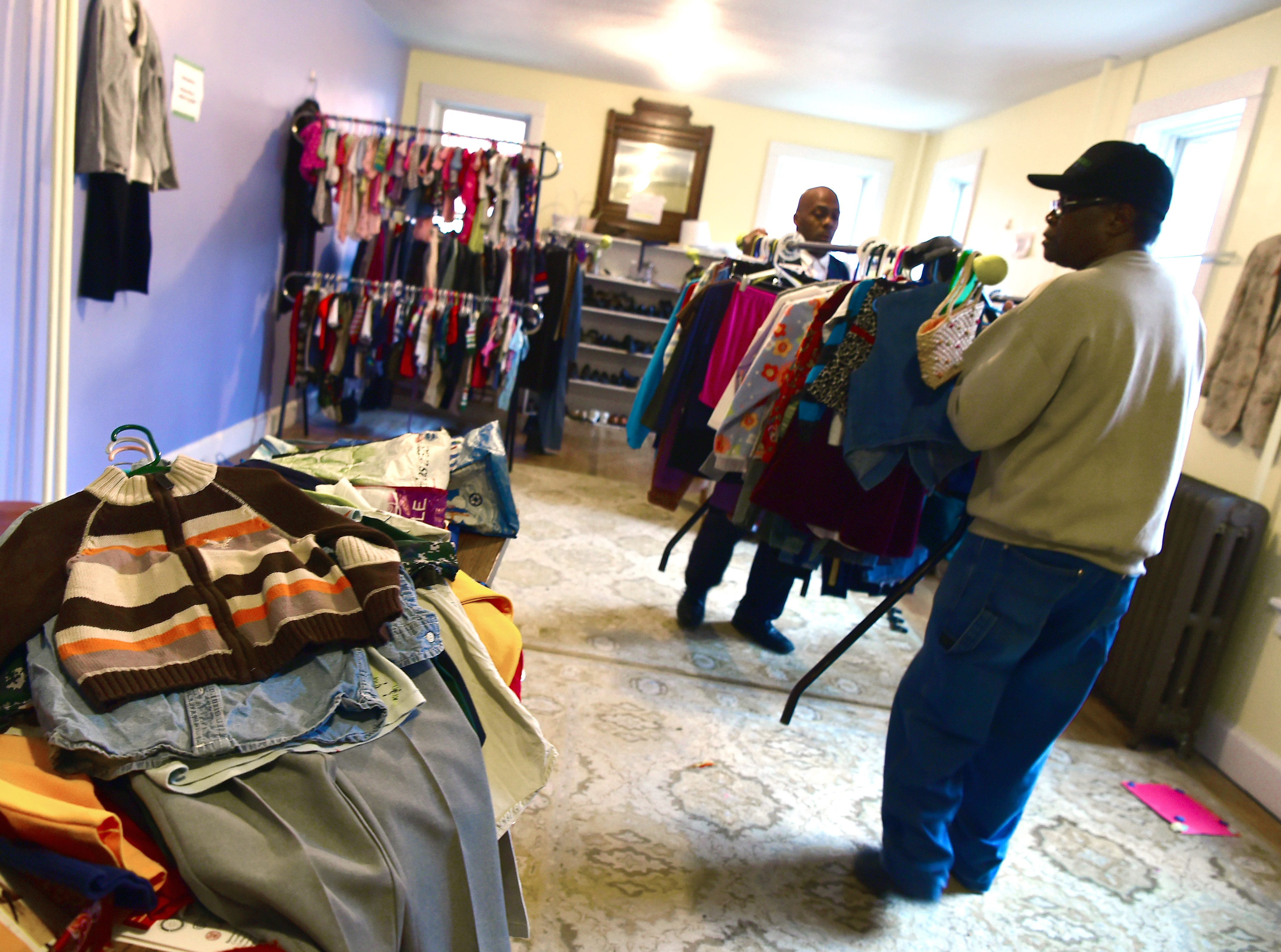 Emmanuel McBean, foreground, and Alex Williams, in back, move racks of clothes as Catholic Charities of Tompkins/Tioga staff and volunteers work at readying winter clothing donations in Ithaca on Thursday, November 29, 2018.