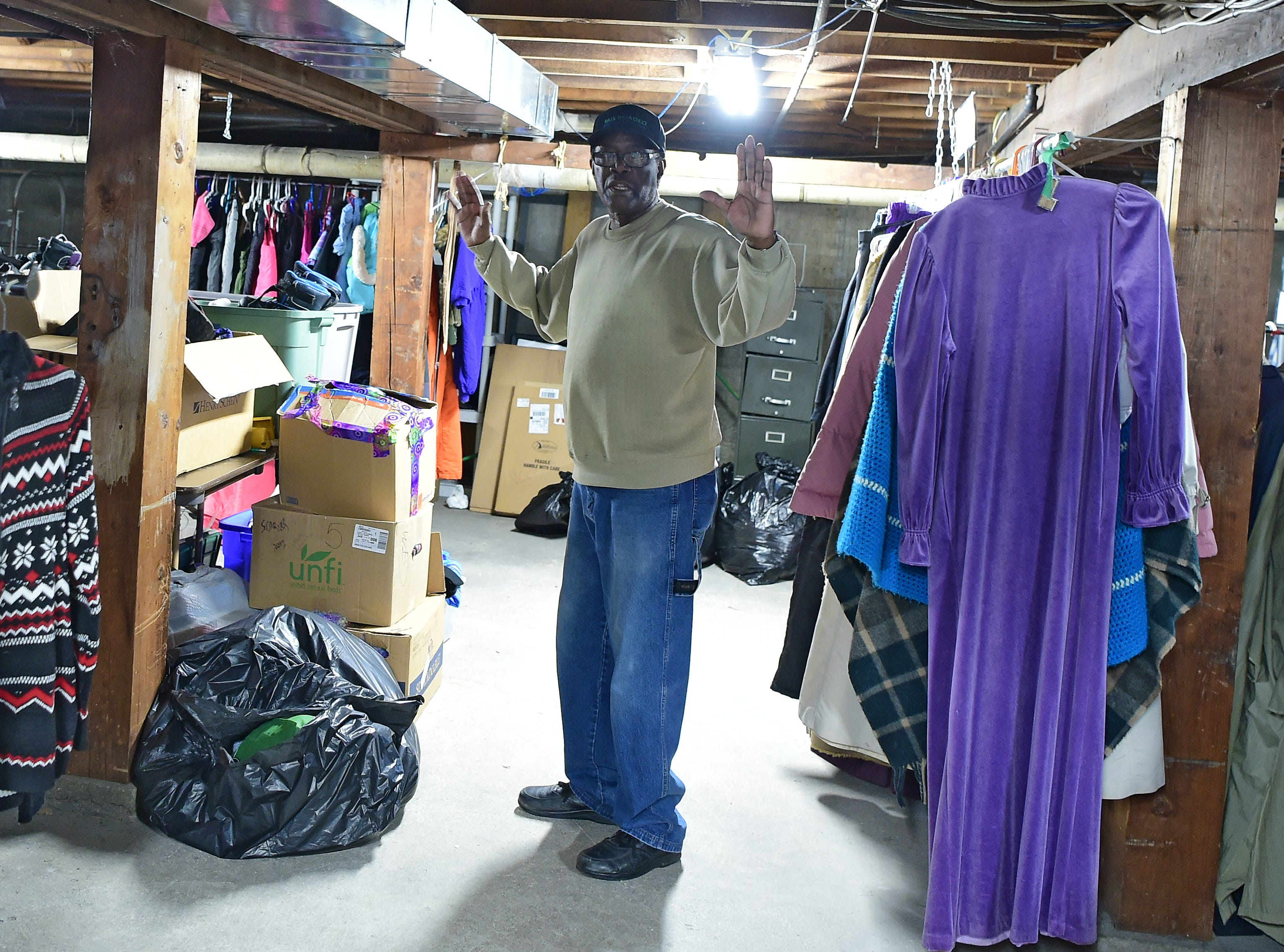 Emmanuel McBean with some of the donated winter clothes. Catholic Charities of Tompkins/Tioga staff and volunteers work at readying winter clothing donations in Ithaca on Thursday, November 29, 2018.