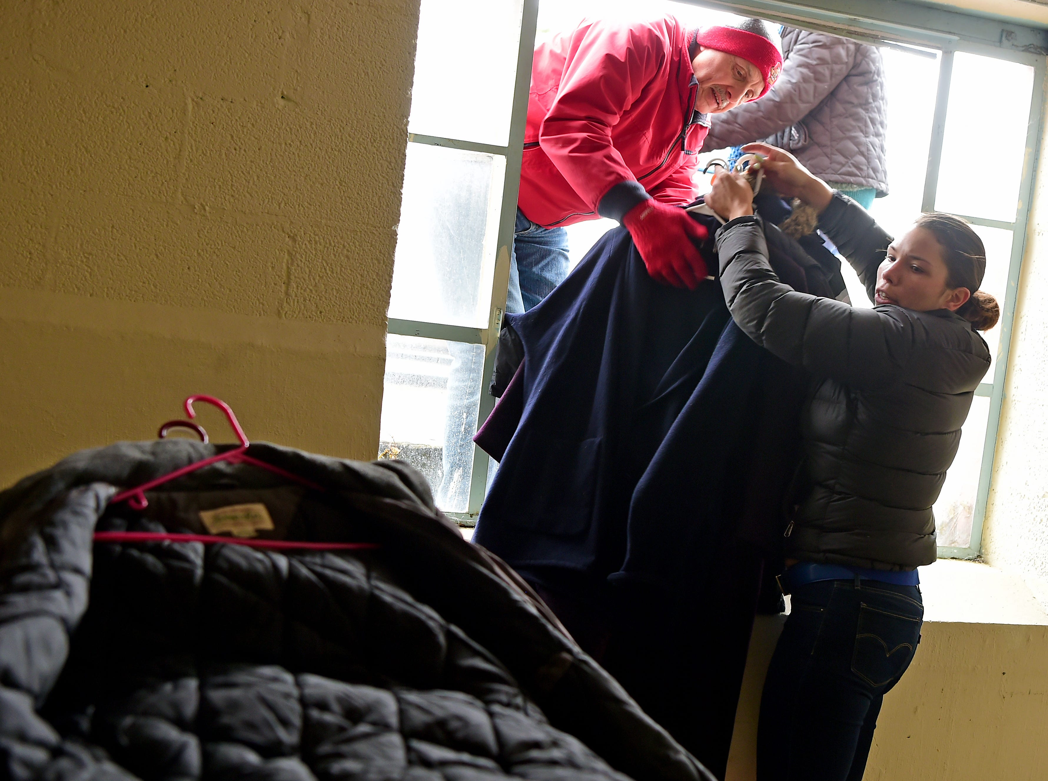 Volunteer Ed Pasto of Lansing, and Catholic Charities caseworker Shay Washington organize donated winter clothing donations in Ithaca on Thursday, November 29, 2018.