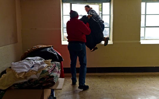 Shay Washington, a Catholic Charities caseworker, and volunteer Ed Pasto of Lansing, organize donated winter clothing donations in Ithaca on Thursday, November 29, 2018.