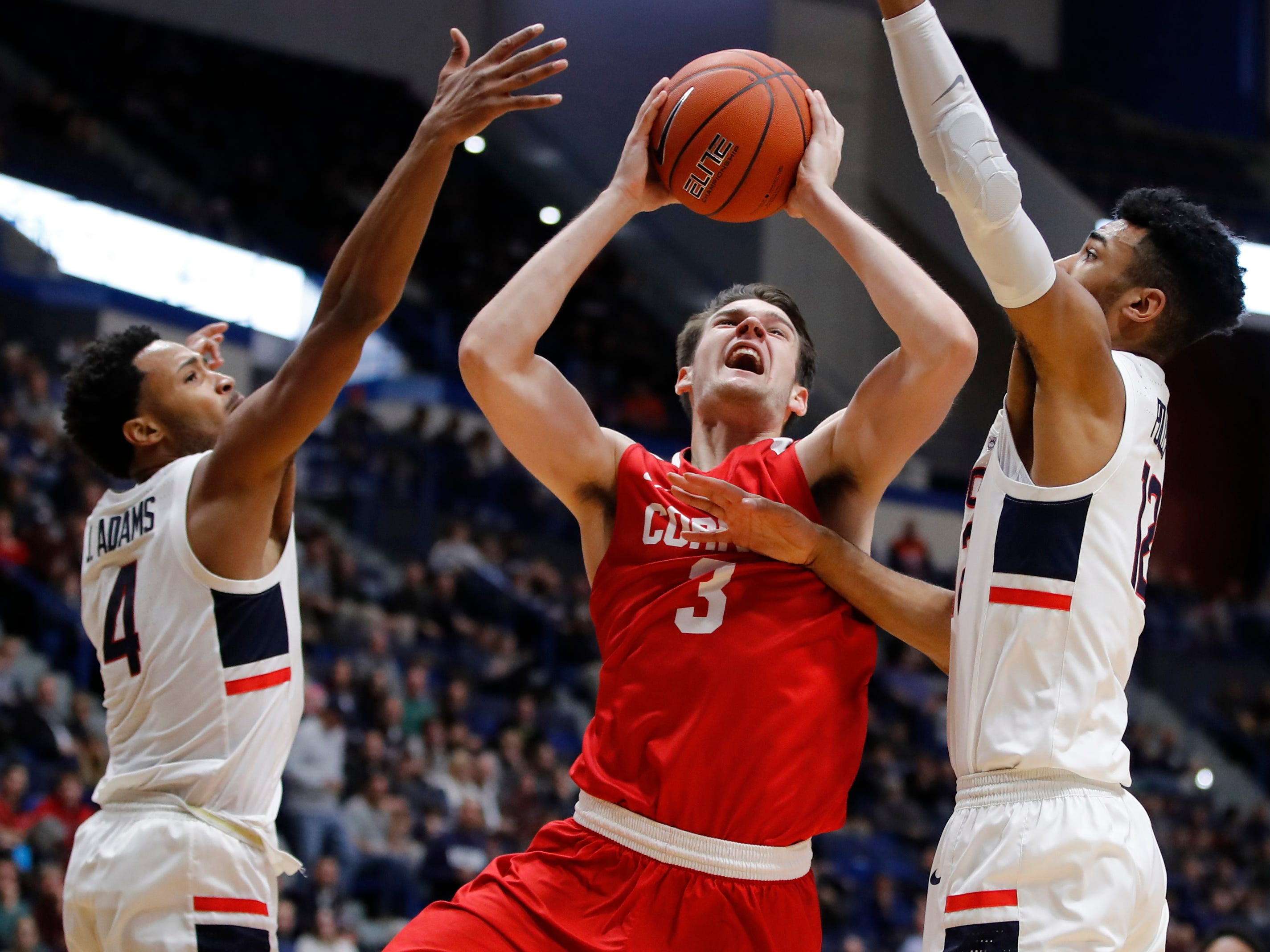 Nov 20, 2018; Storrs, CT, USA; Cornell Big Red forward Jimmy Boeheim (3) shoots between Connecticut Huskies guard Jalen Adams (4) and forward Tyler Polley (12) in the second half at XL Center. UConn defeated Cornell 91-74. Mandatory Credit: David Butler II-USA TODAY Sports