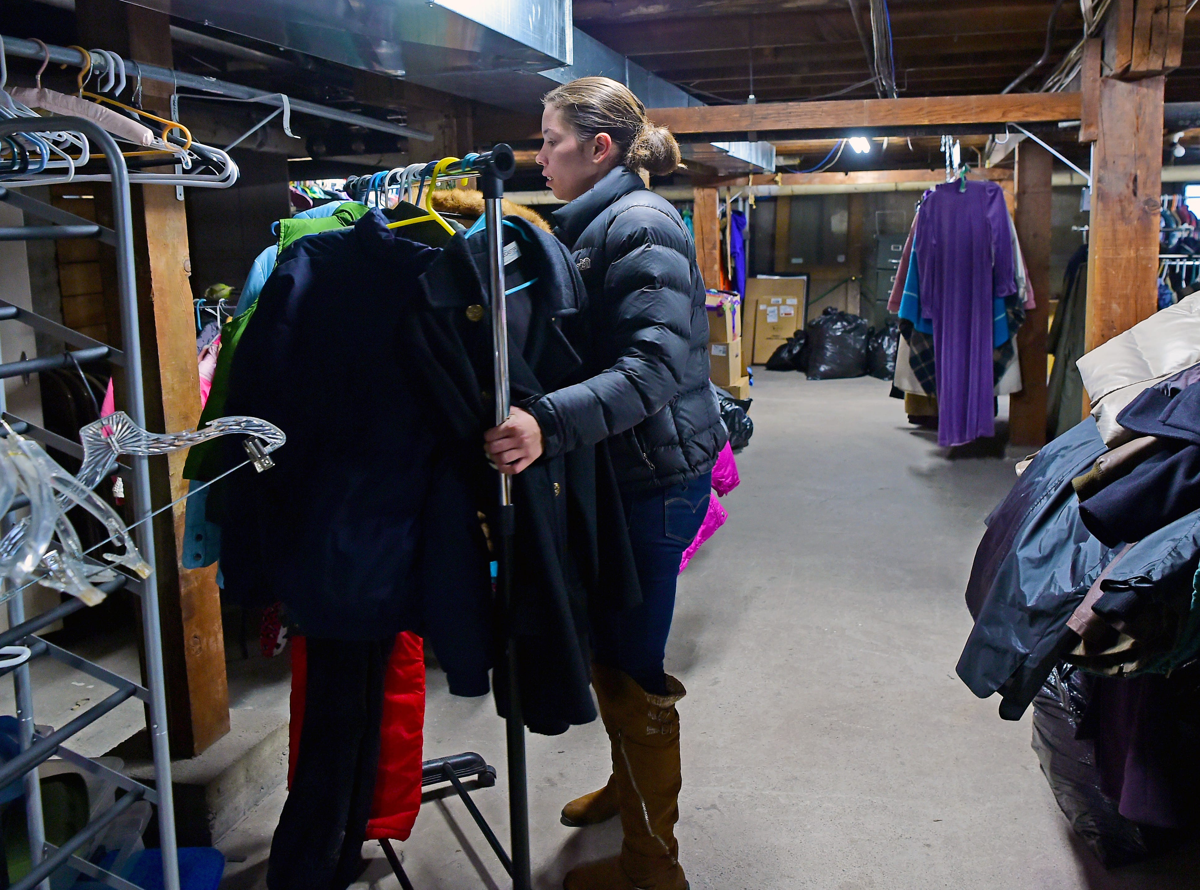 Shay Washington, a Catholic Charities caseworker, readies donated winter clothing donations in Ithaca on Thursday, November 29, 2018.