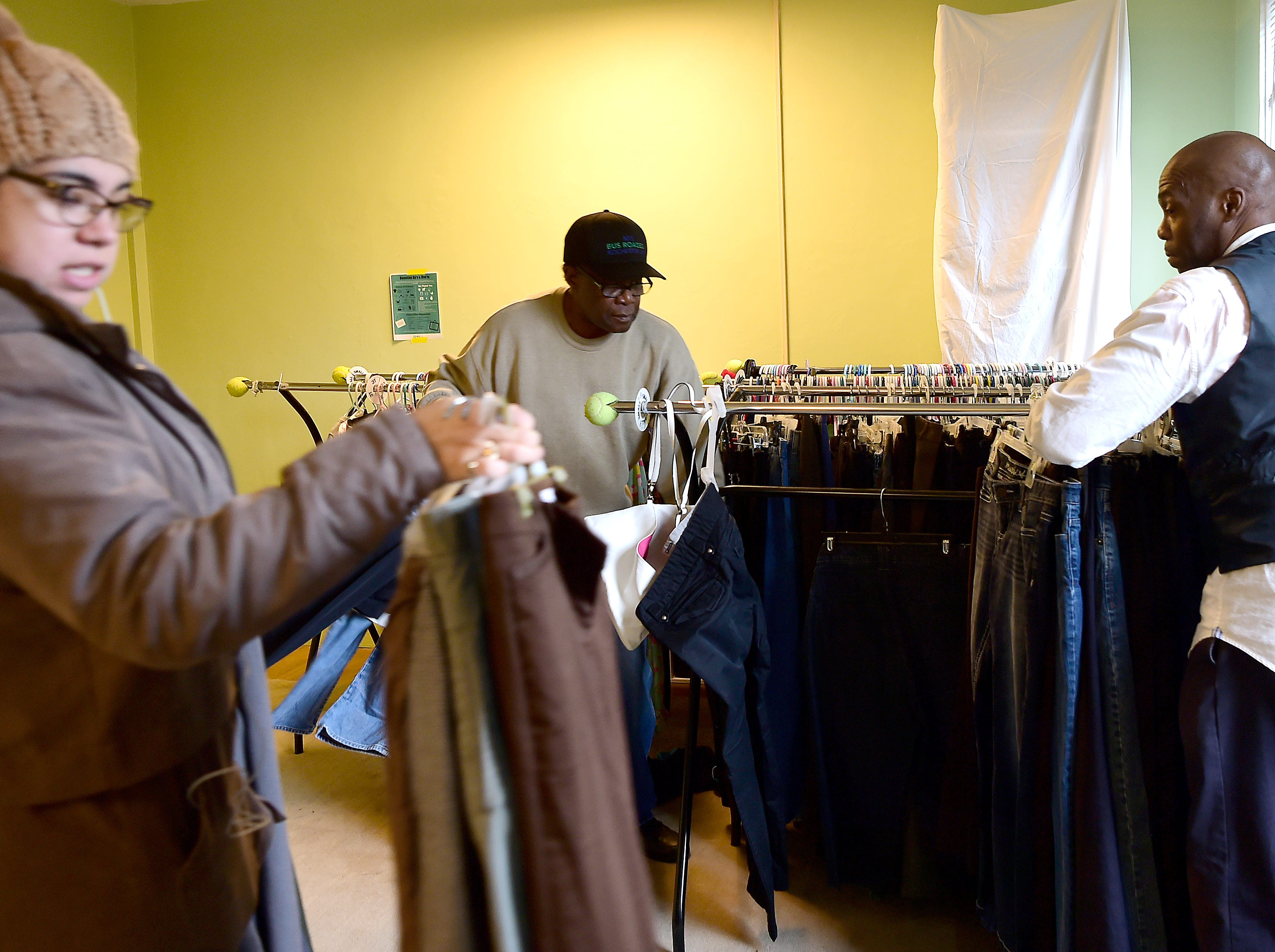 Jessica Estrada, Emmanuel McBean and Alex Williams move racks of clothes as Catholic Charities of Tompkins/Tioga staff and volunteers work at readying winter clothing donations in Ithaca on Thursday, November 29, 2018.