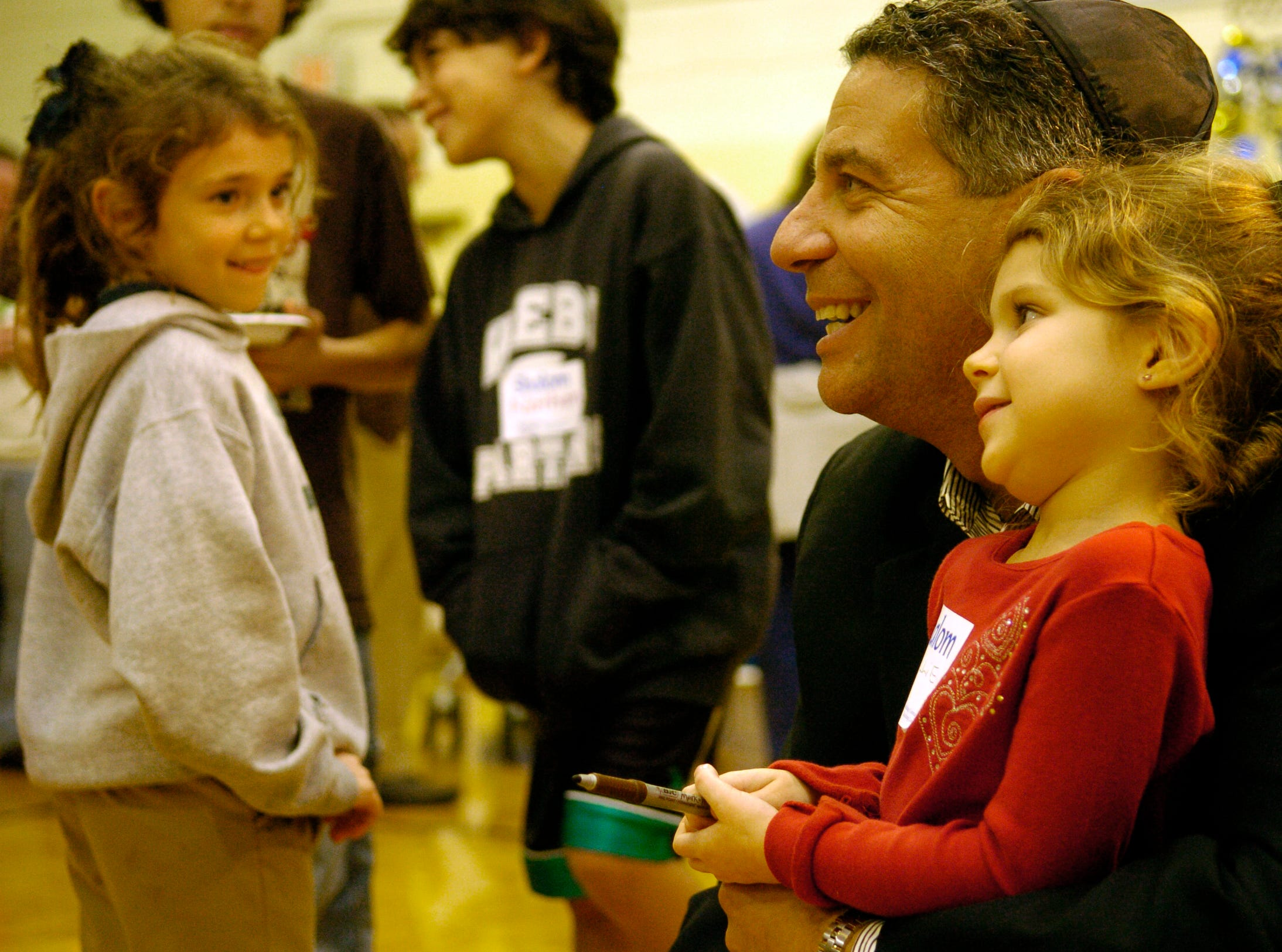 Tuesday,December 11,2007  The University of Tennessee men's basketball coach Bruce Pearl has his photograph take with Hallie Boring, 4, during Menorah Madness at the Arnstein Jewish Community Center. At left is Arielle Rosen, 8, who watches the exchange after having her shirt autographed by Pearl.