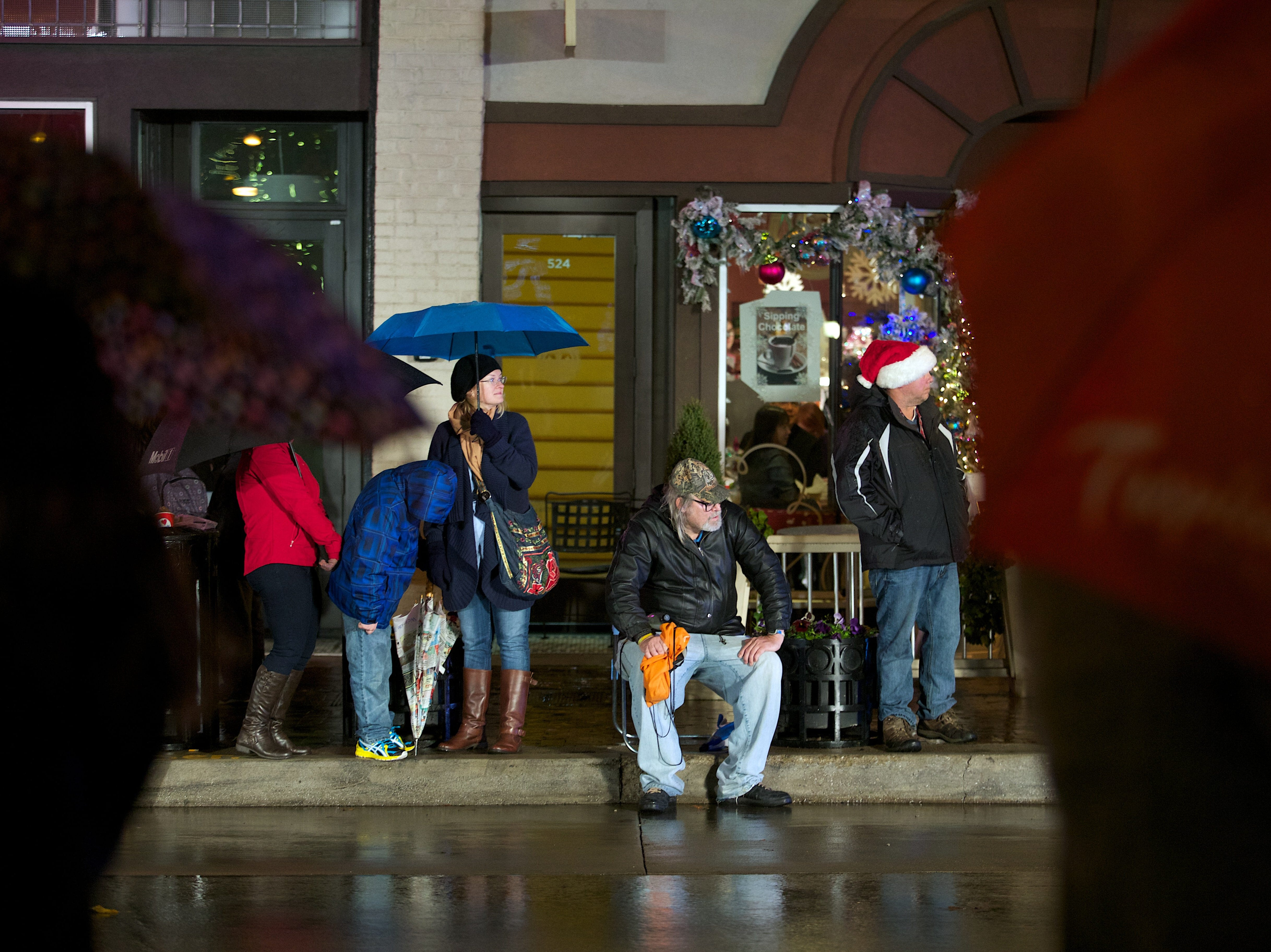 Eugene Cooper, center, waits along Gay Street in the rain for the start of the WIVK Christmas Parade in Knoxville, Tenn. on Friday, December 6, 2013.