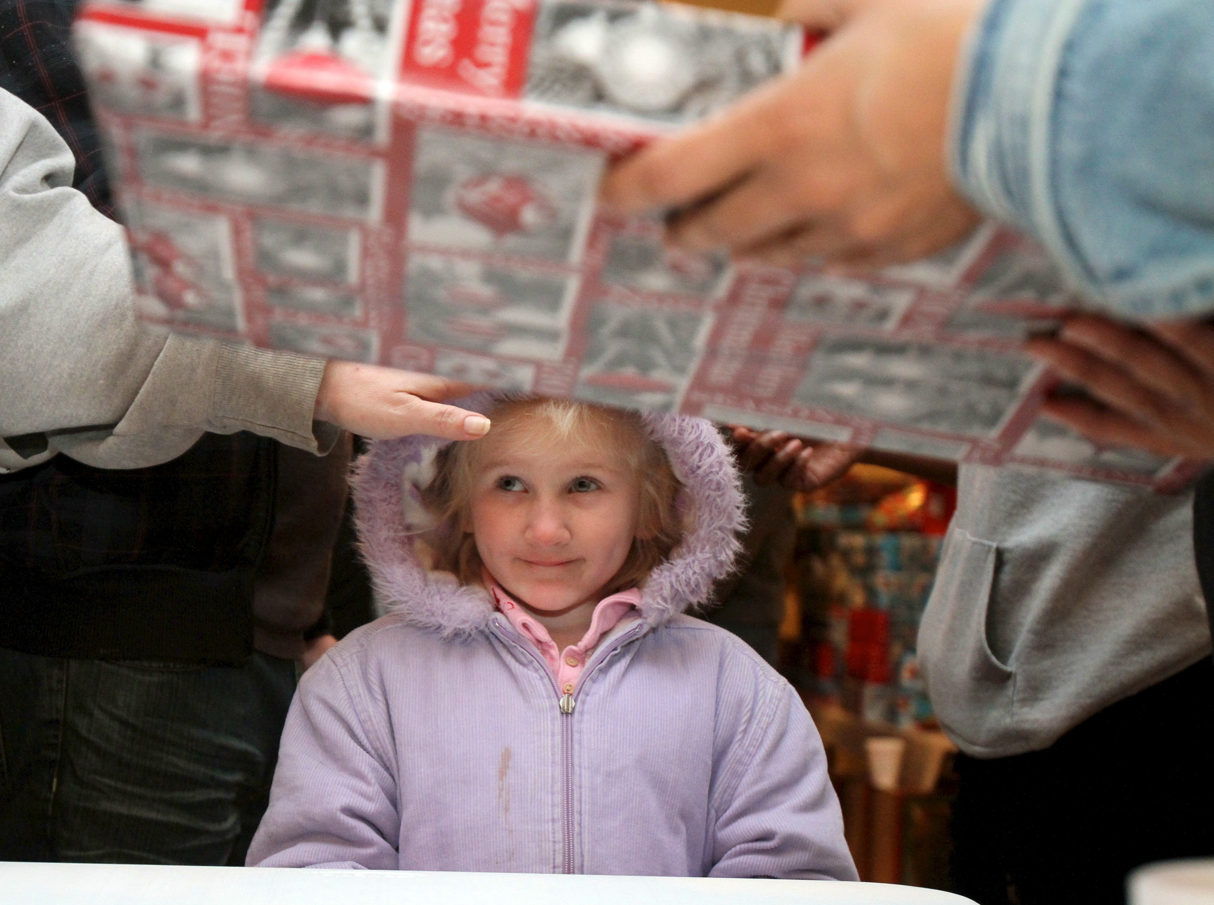 Abigail Bailey, 5, waits to receive a present on Sunday, December 18, 2011 at Overcoming Believers Church. More than 2000 toys were given out by the church to families for Christmas.