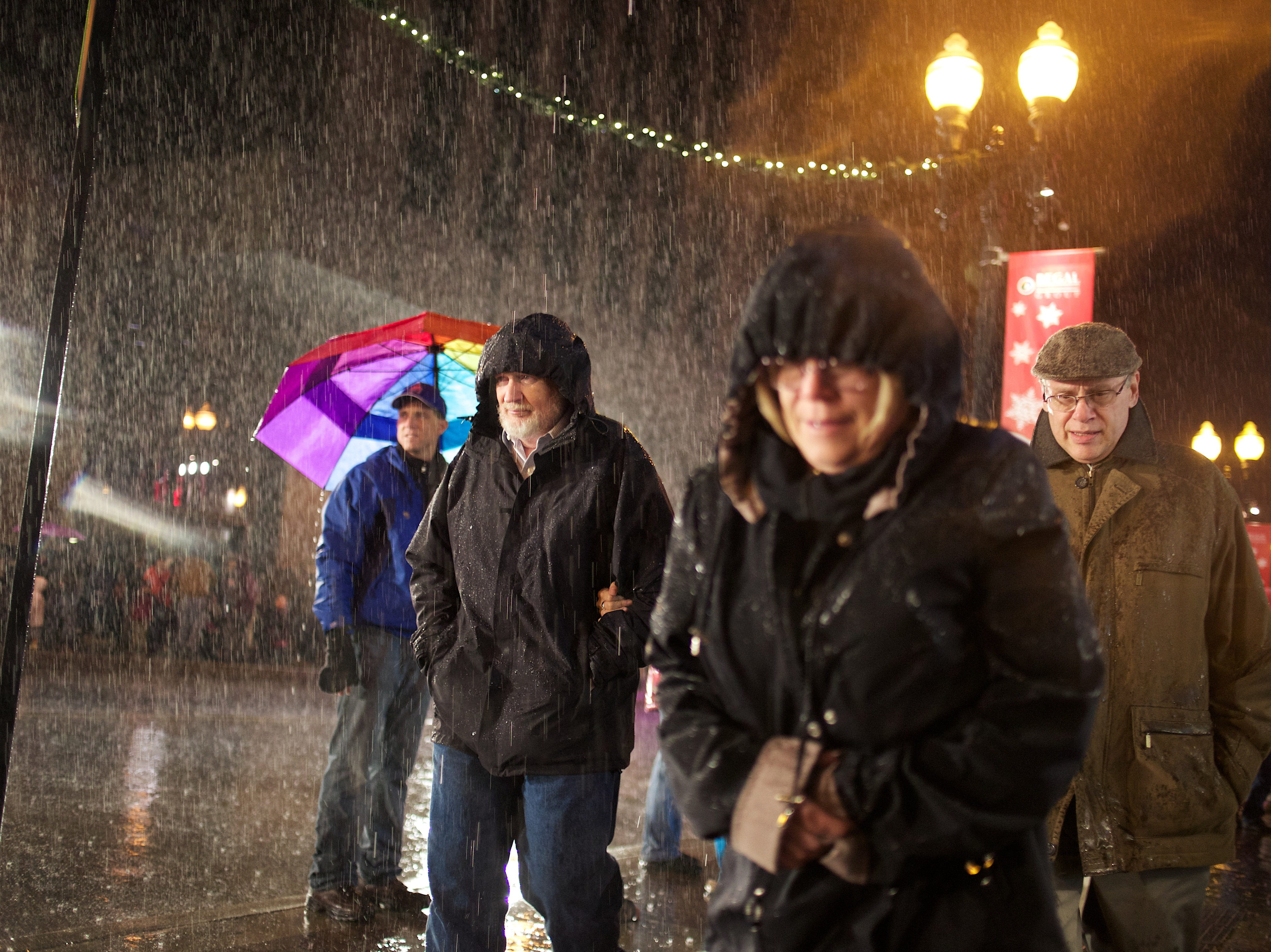 Parade spectators are seen leaving the WIVK Christmas Parade in the rain on Gay Street in Knoxville, Tenn. on Friday, December 6, 2013.