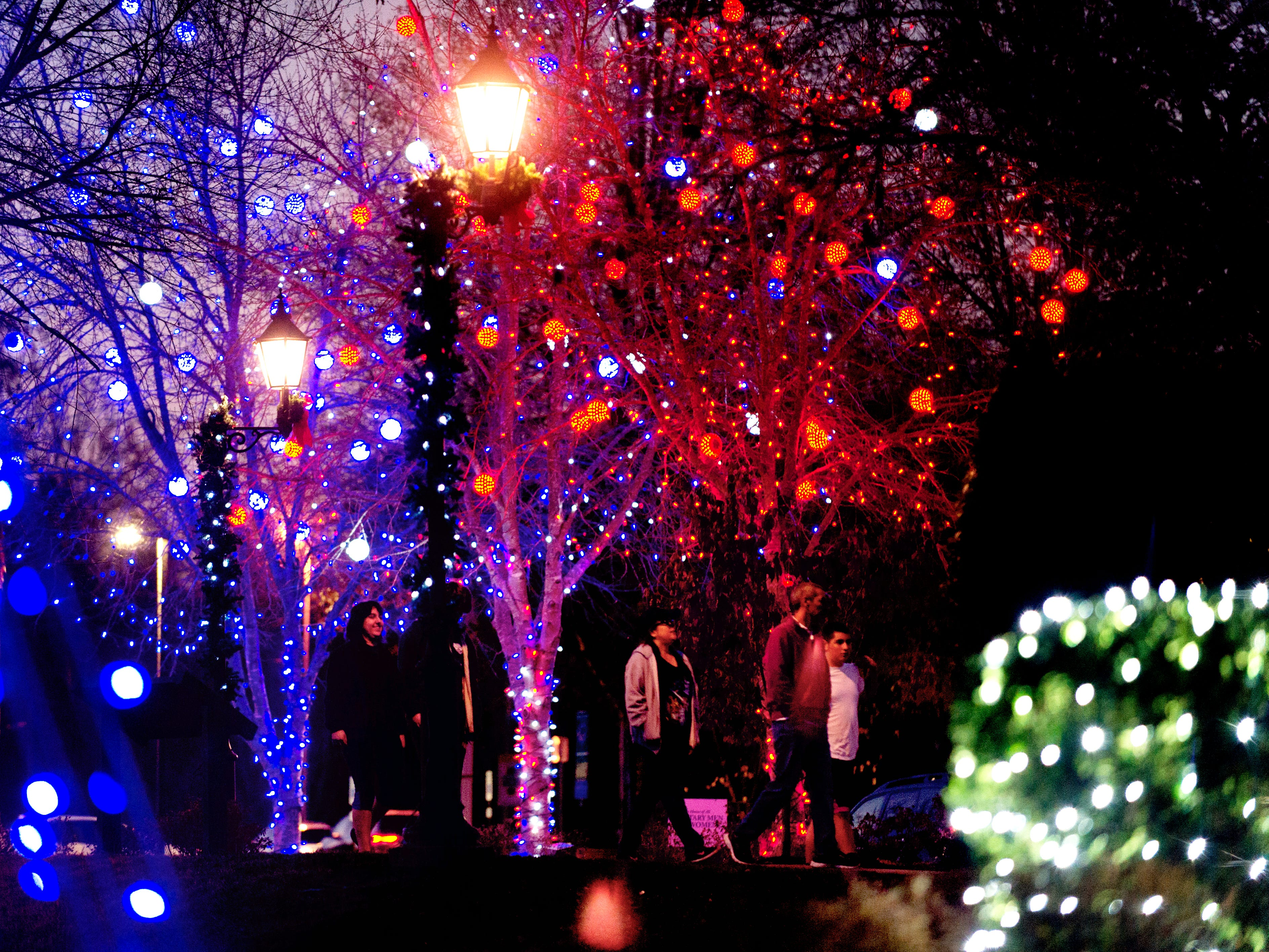 Visitors walk under the lights at the Light the Park Christmas light display at Founders Park in Knoxville, Tennessee on Wednesday, November 29, 2017.