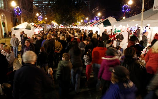People walk past vendors at Market Square on Nov. 25, 2011.